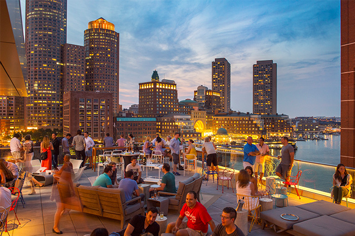 People drink and dine on a restaurant rooftop at dusk, overlooking water and a city skyline