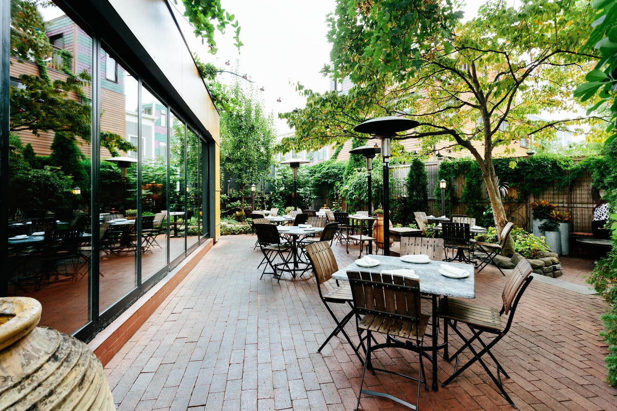 A restaurant patio features lush greenery, heat lamps, a brick surface, and floor-to-ceiling windows looking into the restaurant