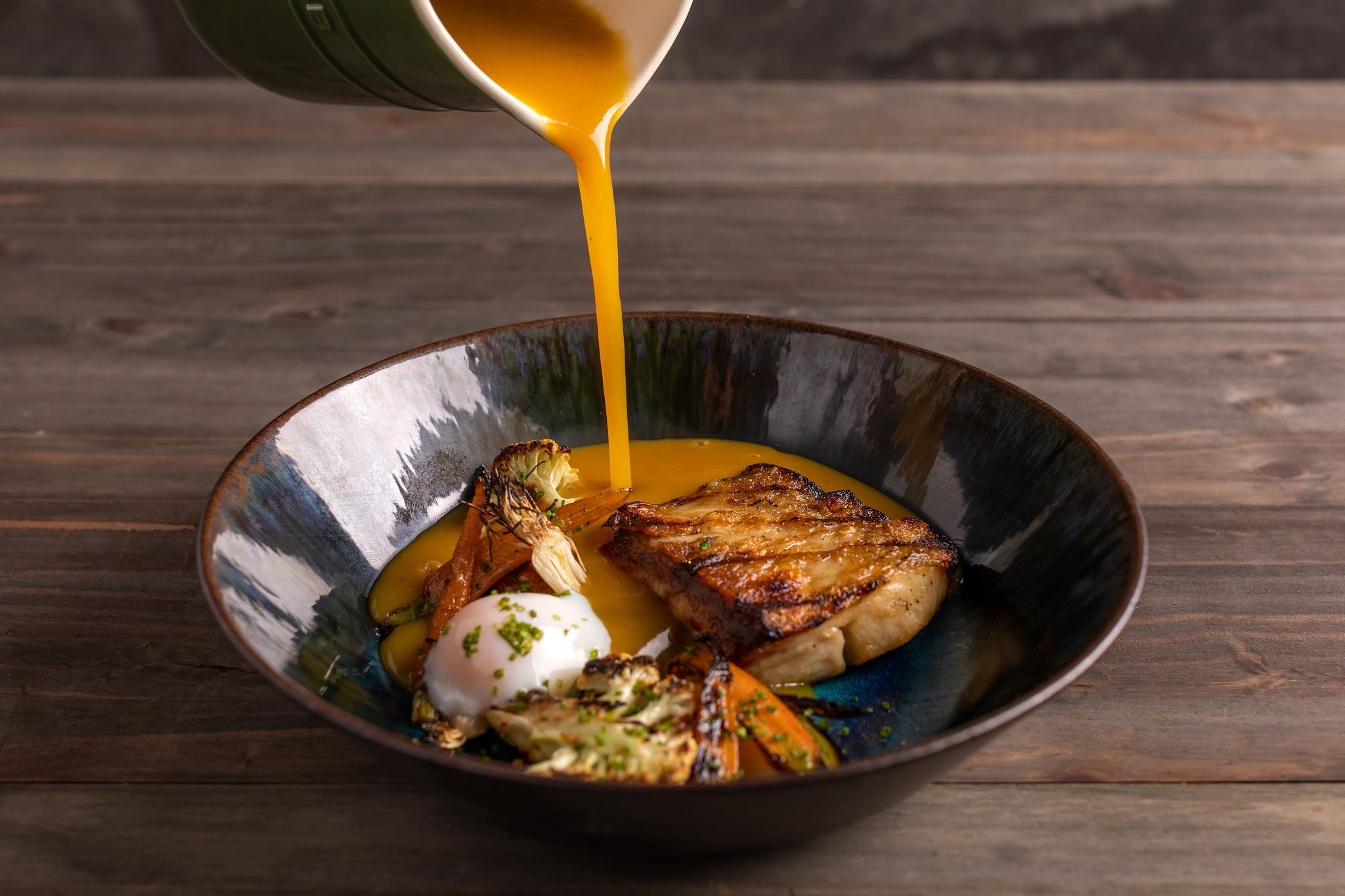 An unseen server pours broth from a serving pitcher into a bowl of tambaqui fish fillet, cauliflower, carrots, and a poached egg. The glazed bowl sits on a dark wooden table.