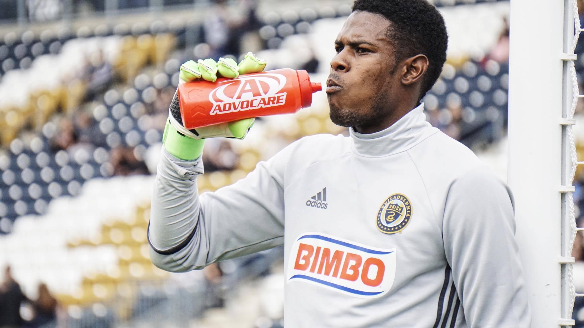 Andre Blake take a drink during warmups.