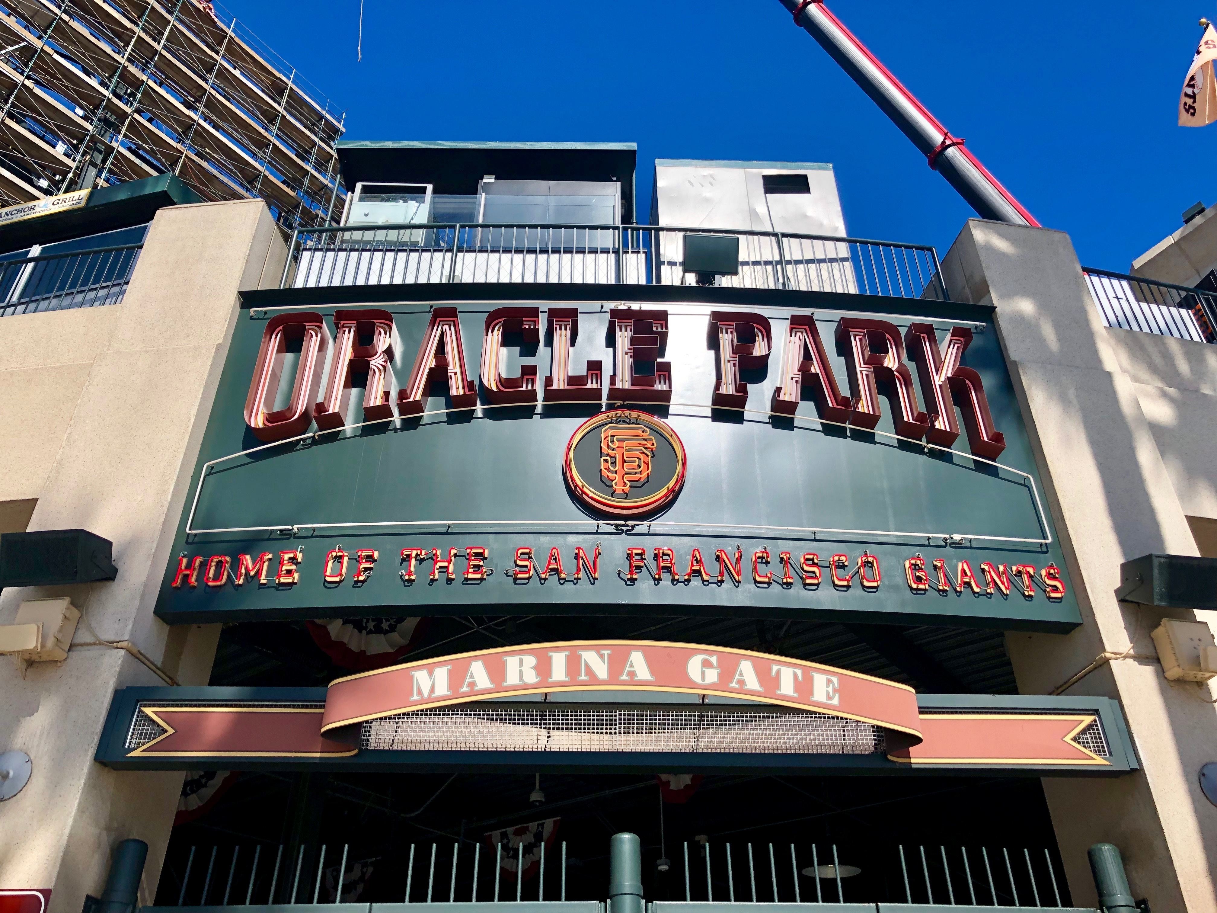 """A low angle photo of a sign reading """"Oracle Park,"""" with the logo of the San Francisco Giants—a stylized letter S and letter F entwined with one another—visible below it."""