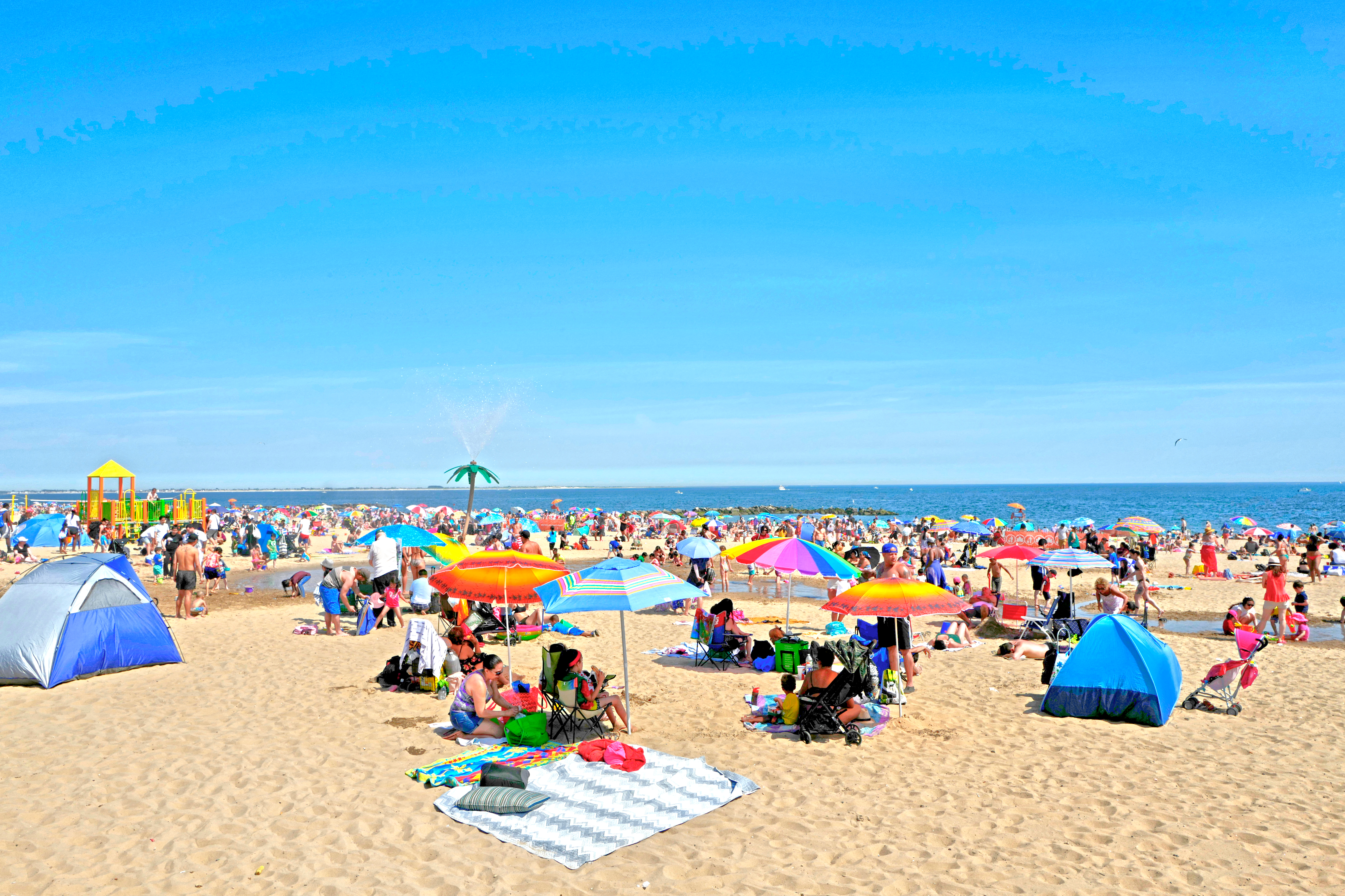 A sandy beach. Many people are on the beach and there are colorful umbrellas and tents. The ocean is in the distance.