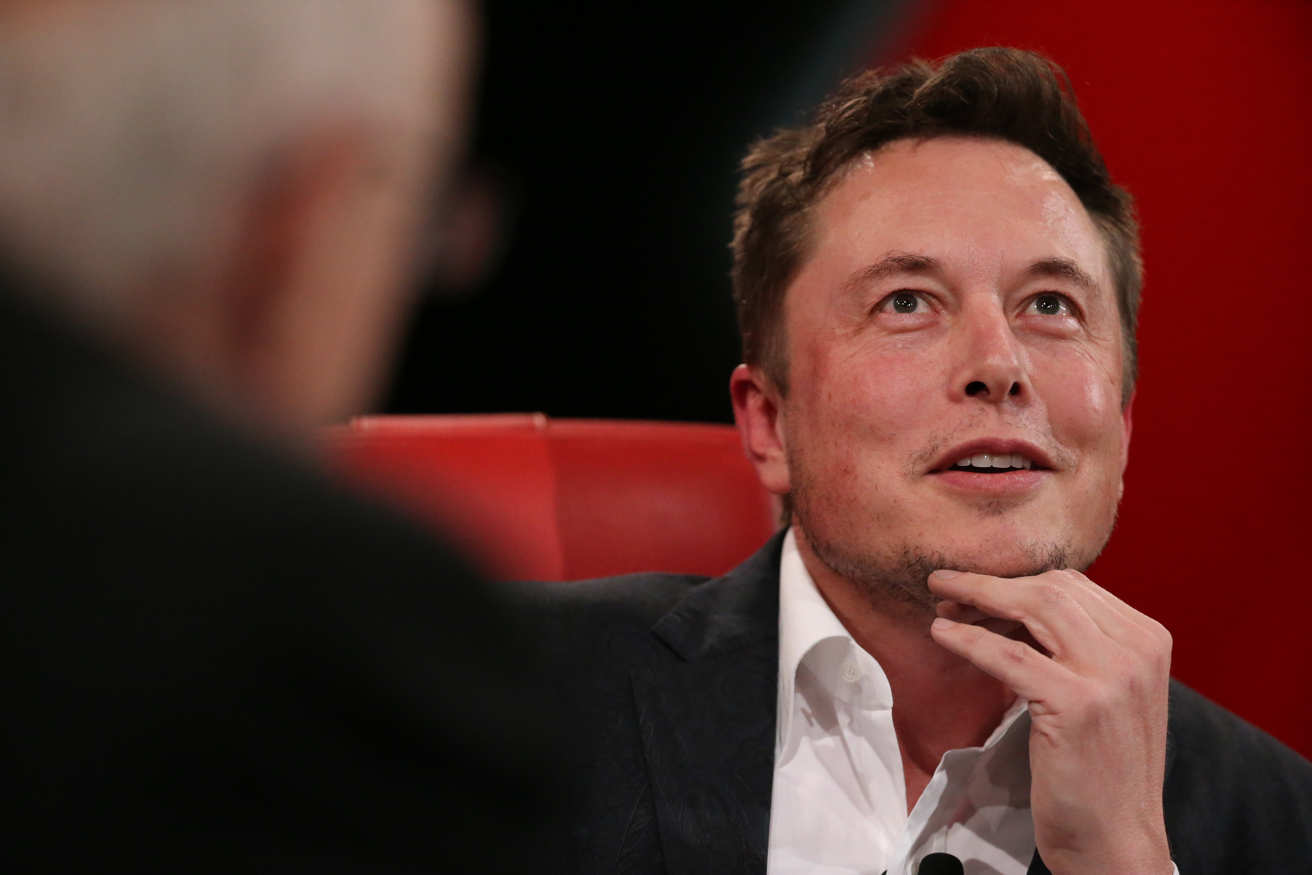 Elon Musk at Code Conference 2016, hand on chin, looking up.