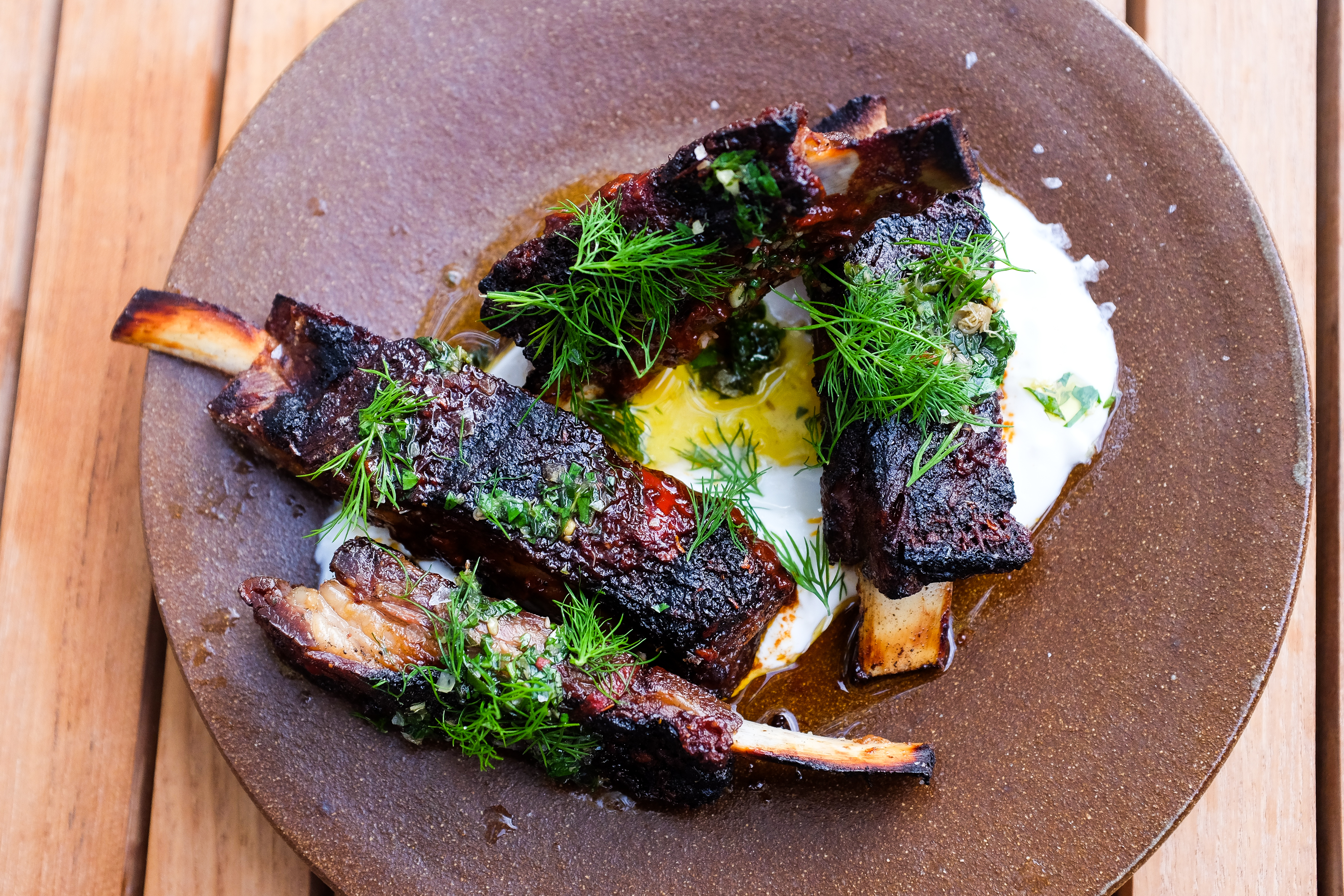 Four ribs on a brown stoneware plate on a bed of creamy yogurt with sprigs of bright green herbs on top.