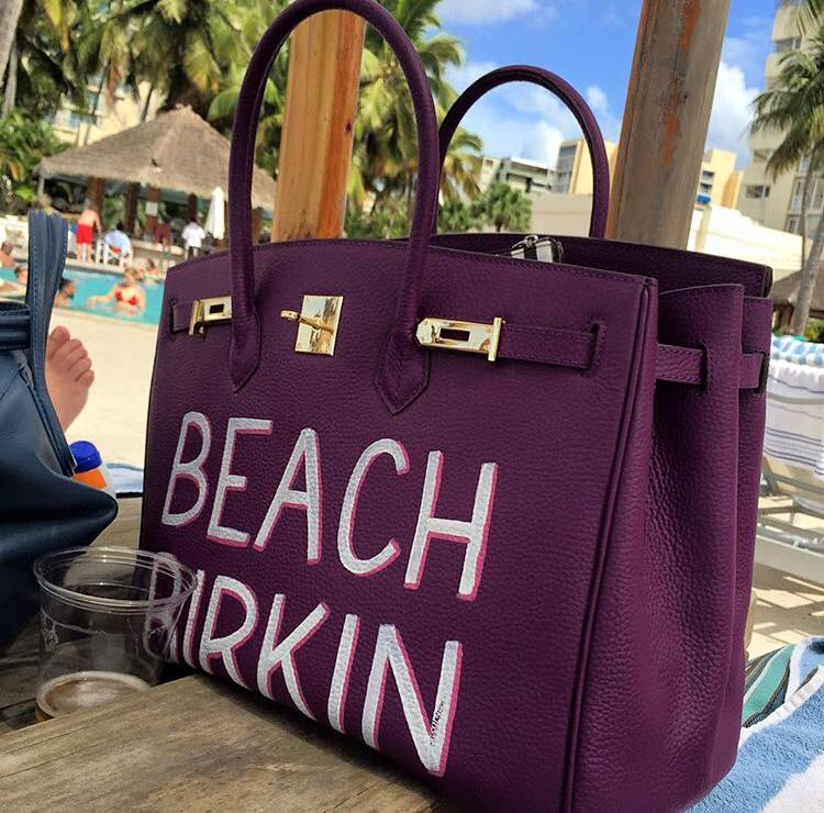 "A purple handbag painted with the words ""Beach Birkin"""