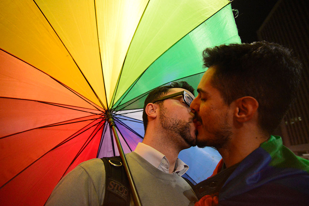 Two men share a kiss during a vigil for the victims in the Pulse nightclub terror attack in Orlando in front of the Masp on June 15, 2016, in Sao Paulo, Brazil.
