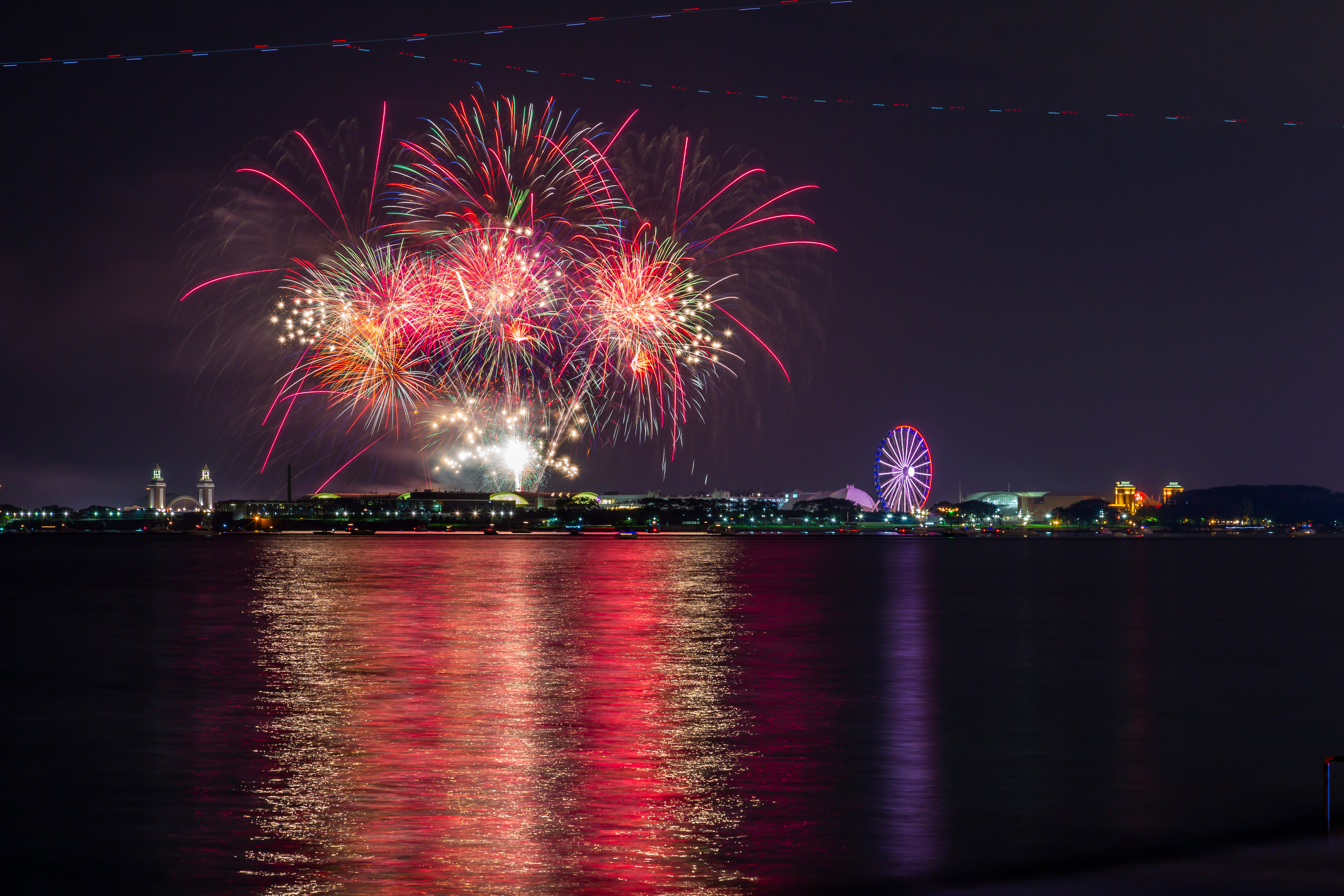 Colorful fireworks explode over Lake Michigan and Navy Pier at night.