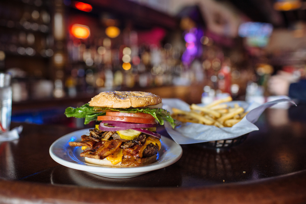A burger on a sesame bun with sliced tomato, red onion, bacon, lettuce, and cheese with a basket of fries.