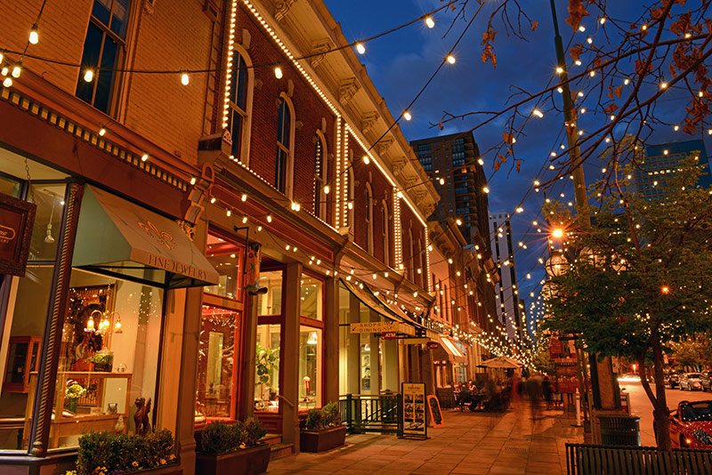 A photo looking down Larimer Square in Denver with storefronts visible and lights hanging overhead
