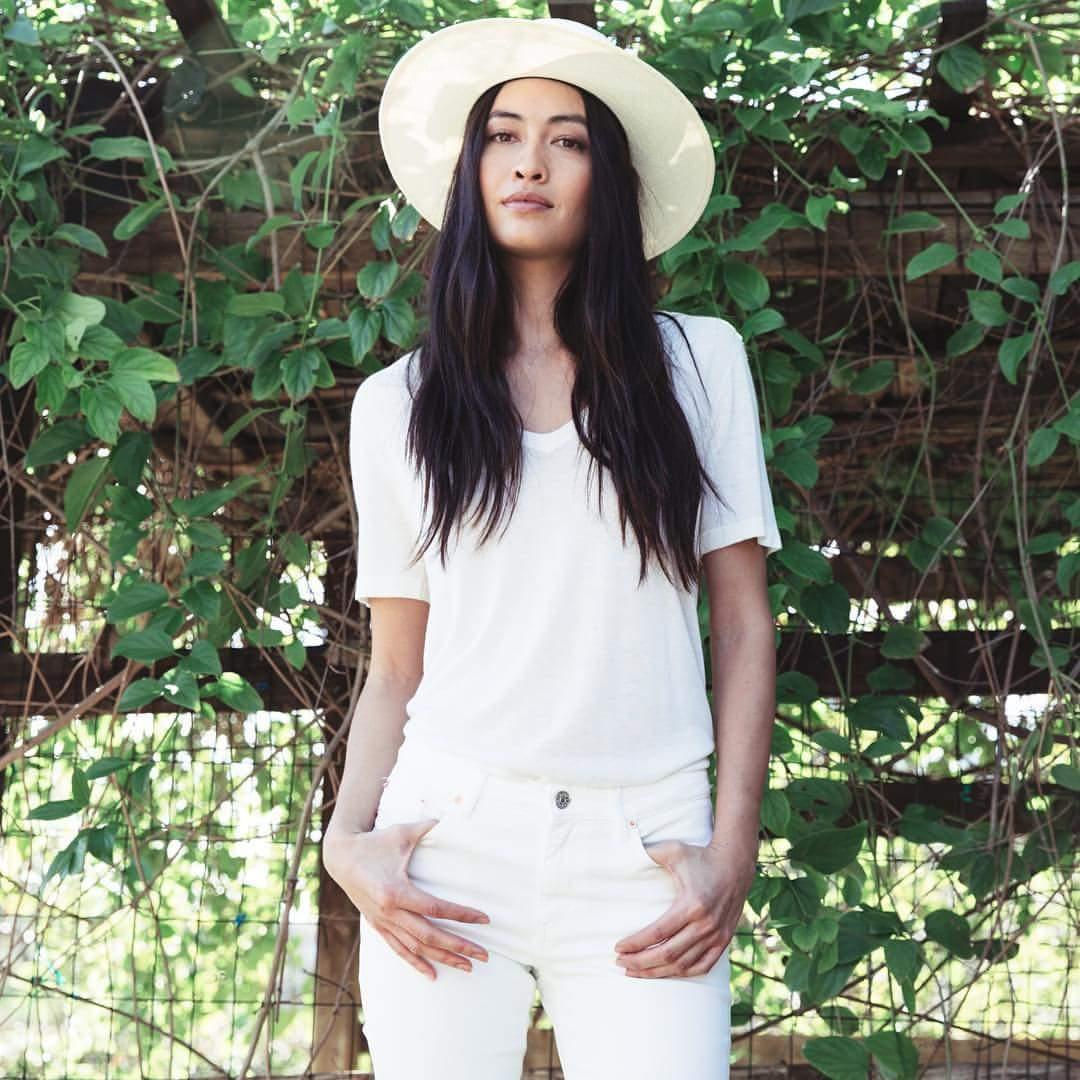 woman wearing white t-shirt, denim, and hat by Jenni Kayne