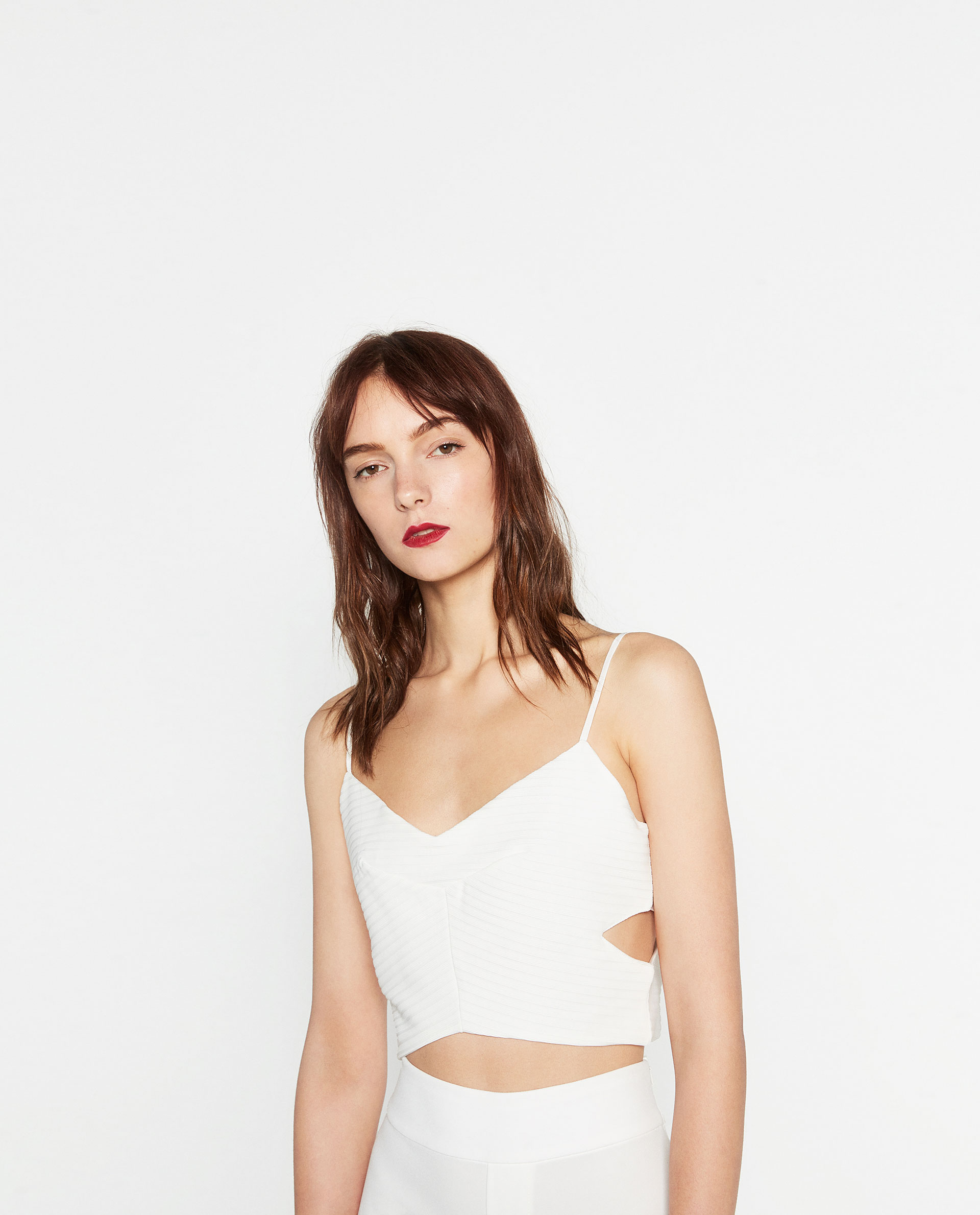 A model in a white crop top with side cutouts