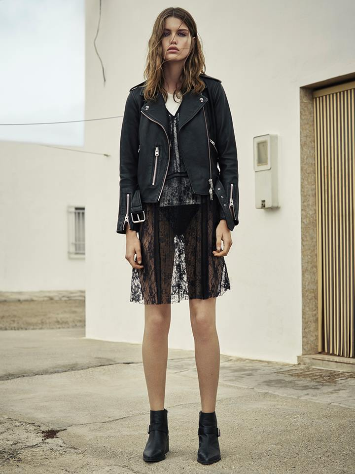Woman wearing black leather jacket with edgy lace dress