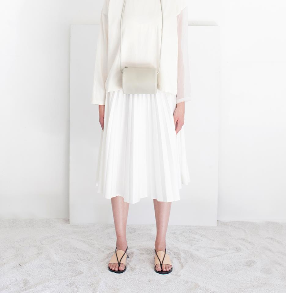 Woman wearing all-white outfit with minimalist bag and sandals by Building Block
