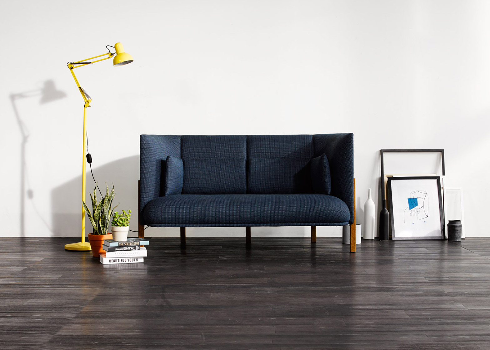A living area scene with a dark blue-upholstered, high-backed sofa, yellow flow lamp with articulated arm, a stack of books, frames, and other small home goods.