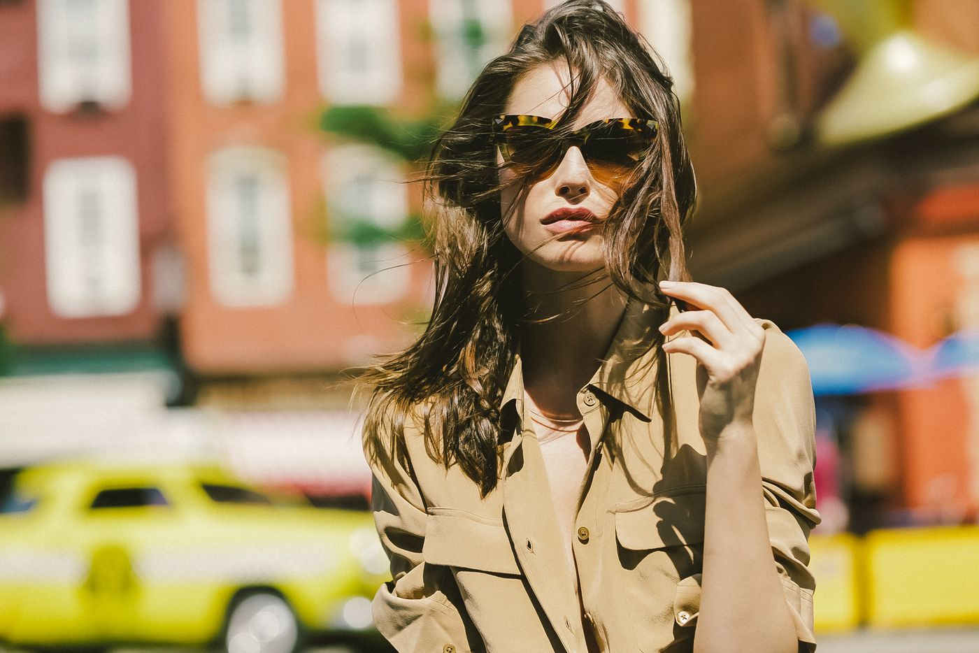 A woman in sunglasses and a tan blouse.