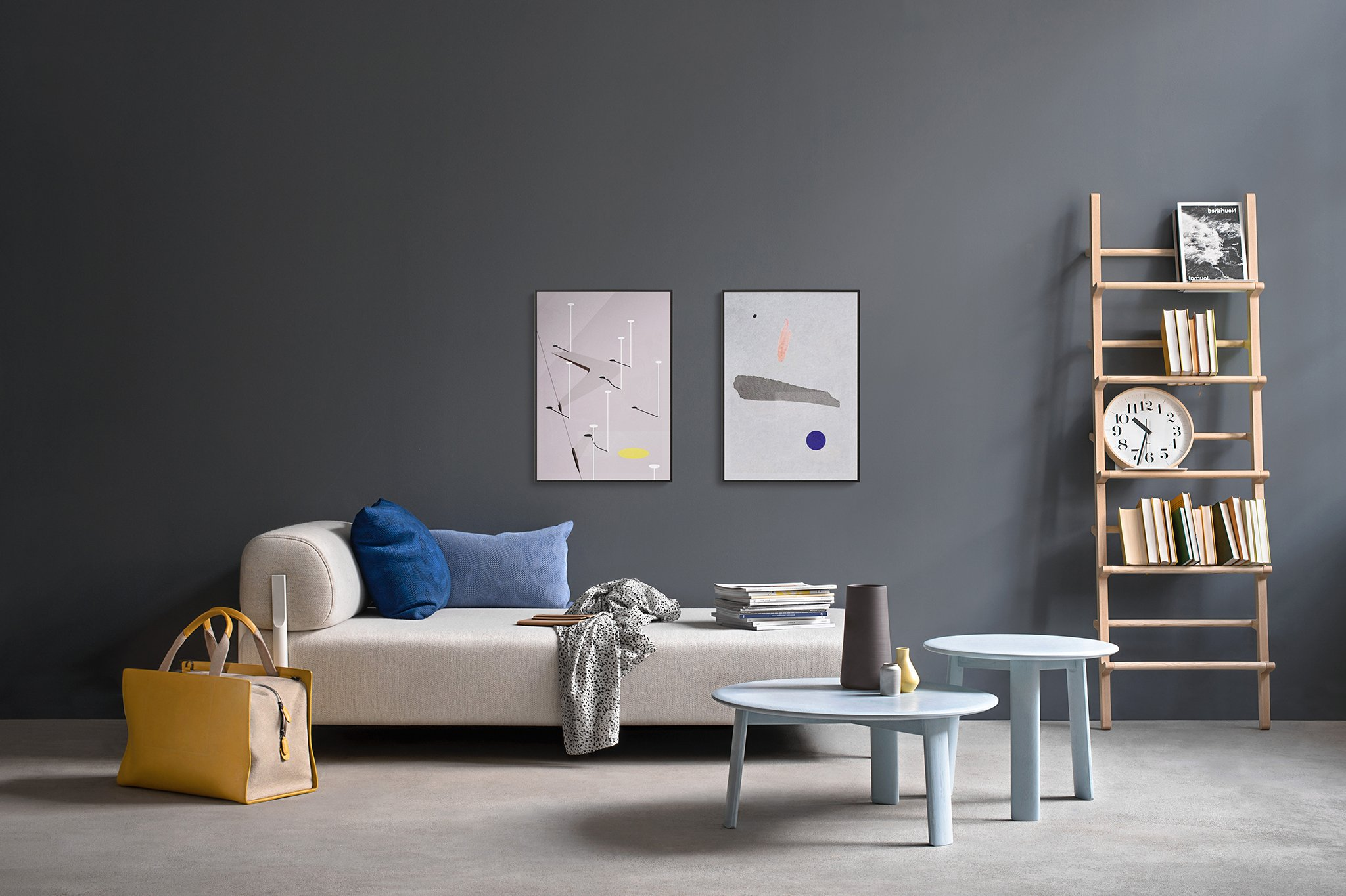 A living room scene featuring a cream-colored couch, two light-blue coffee tables, a ladder shelf holding books, a clock, and a picture, and a yellow weekender bag on the floor off to the side.