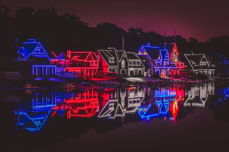A view of Boathouse Row lit up in red, white, and blue lights