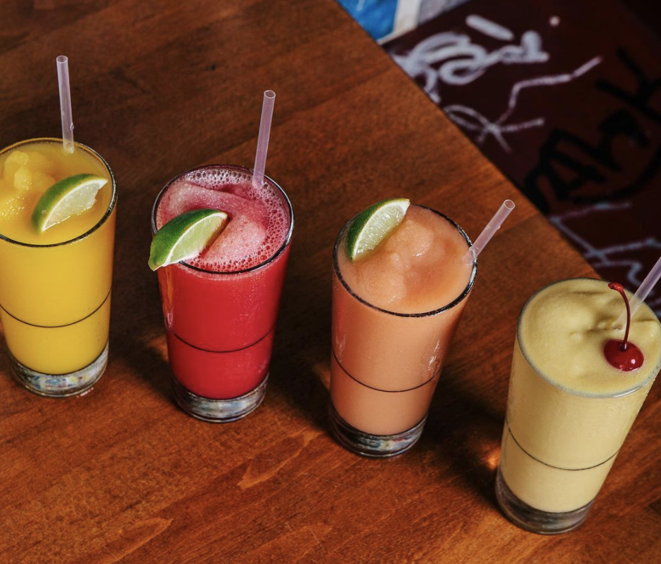 Four frozen drinks in tall pint glasses in a variety of flavors on a wood table.