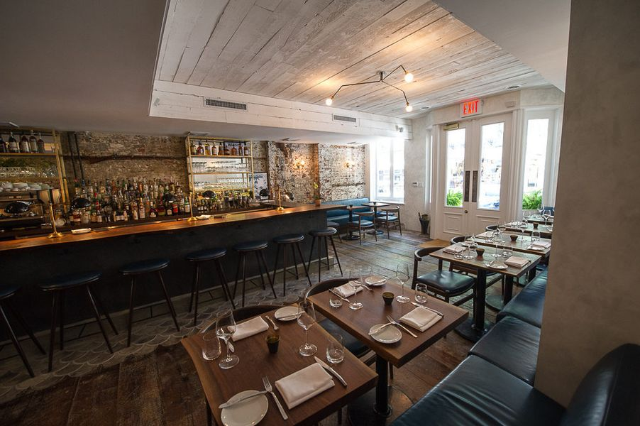 Open light pours into the Musket Room's front dining room, filled with tables for two and a bar on the far side of the photo