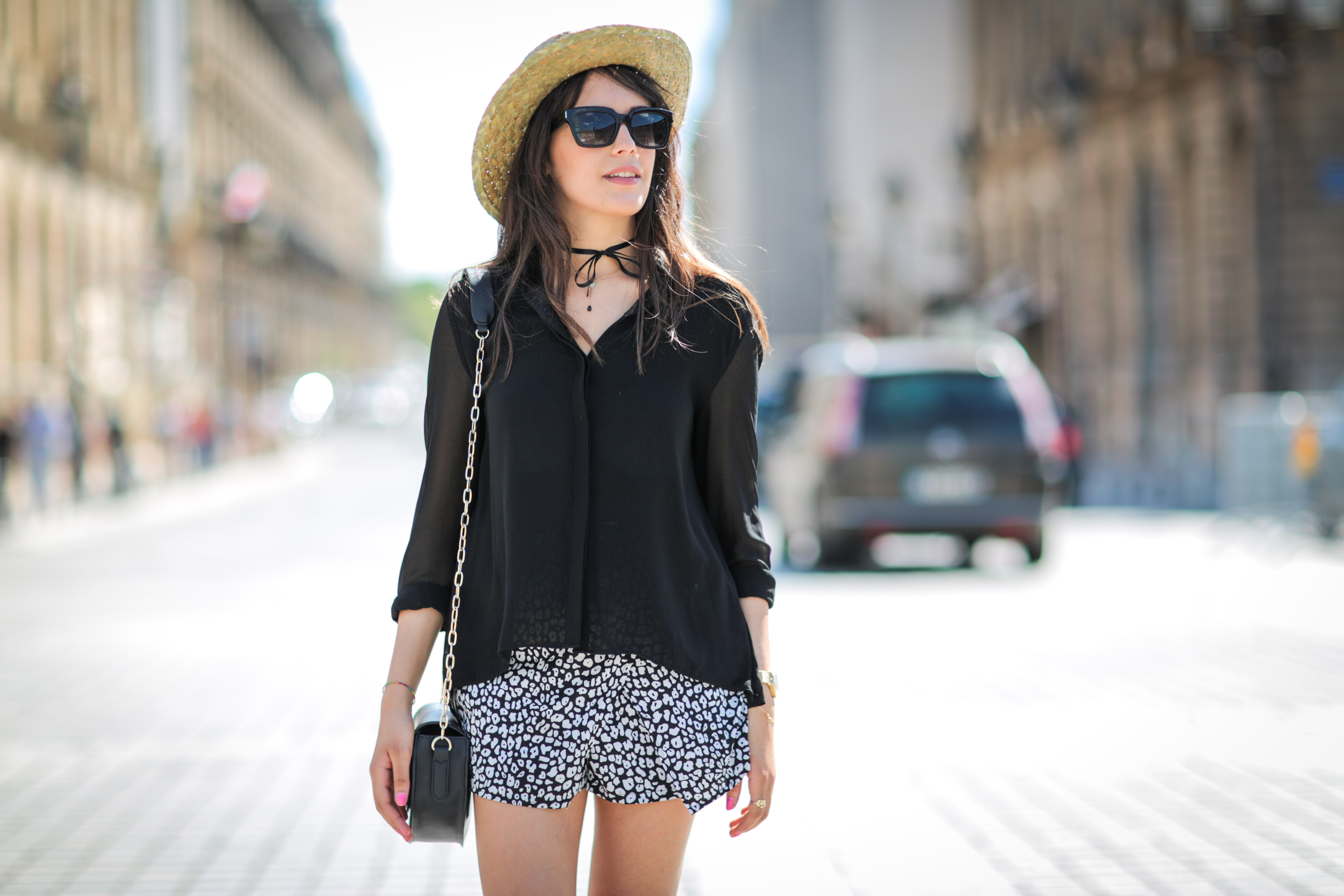 A woman wears a straw hat with a black top and shorts.