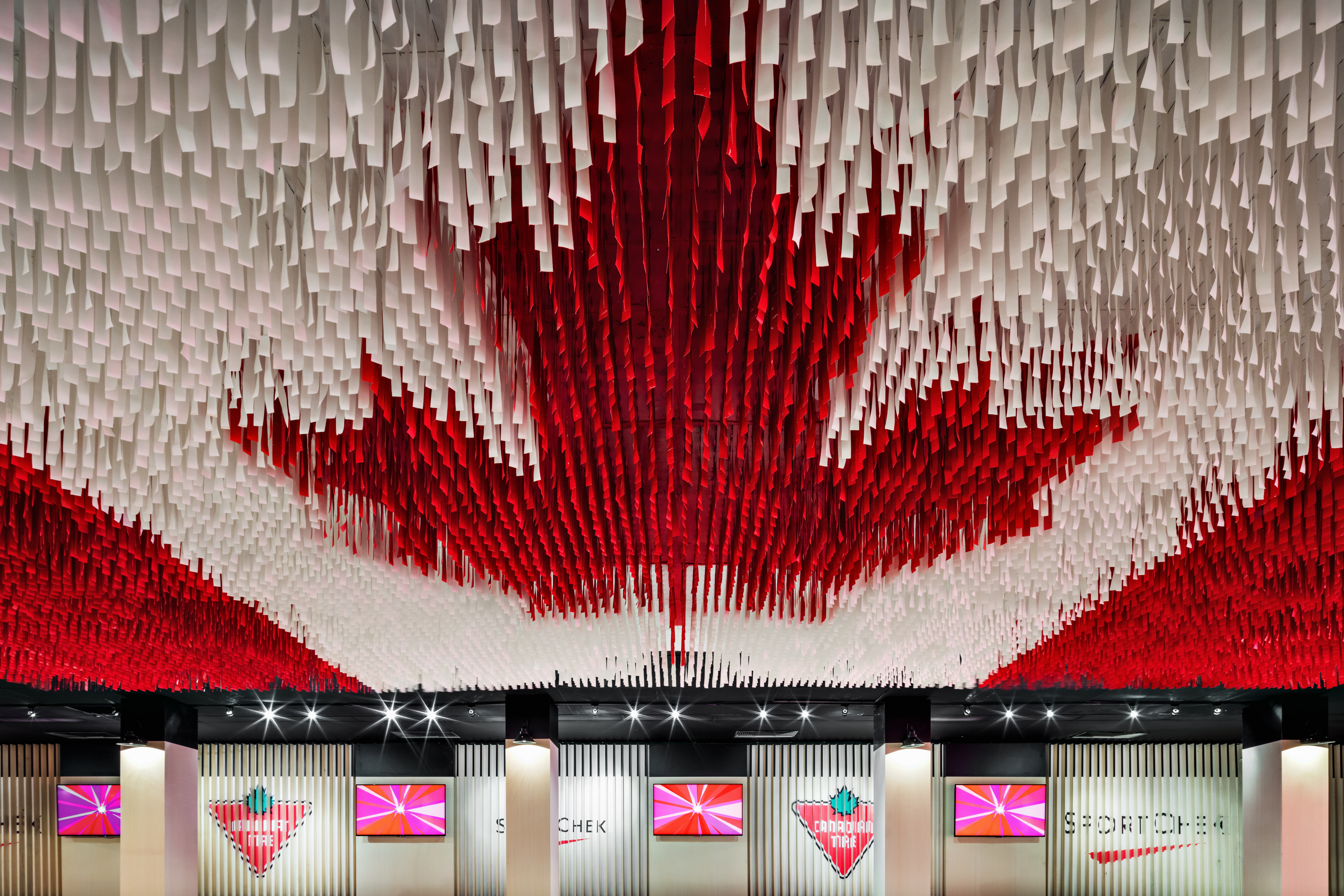 This deconstructed Canadian flag is made up of hundreds of hanging ribbons and is suspended from the ceiling of the Celebration Lounge.