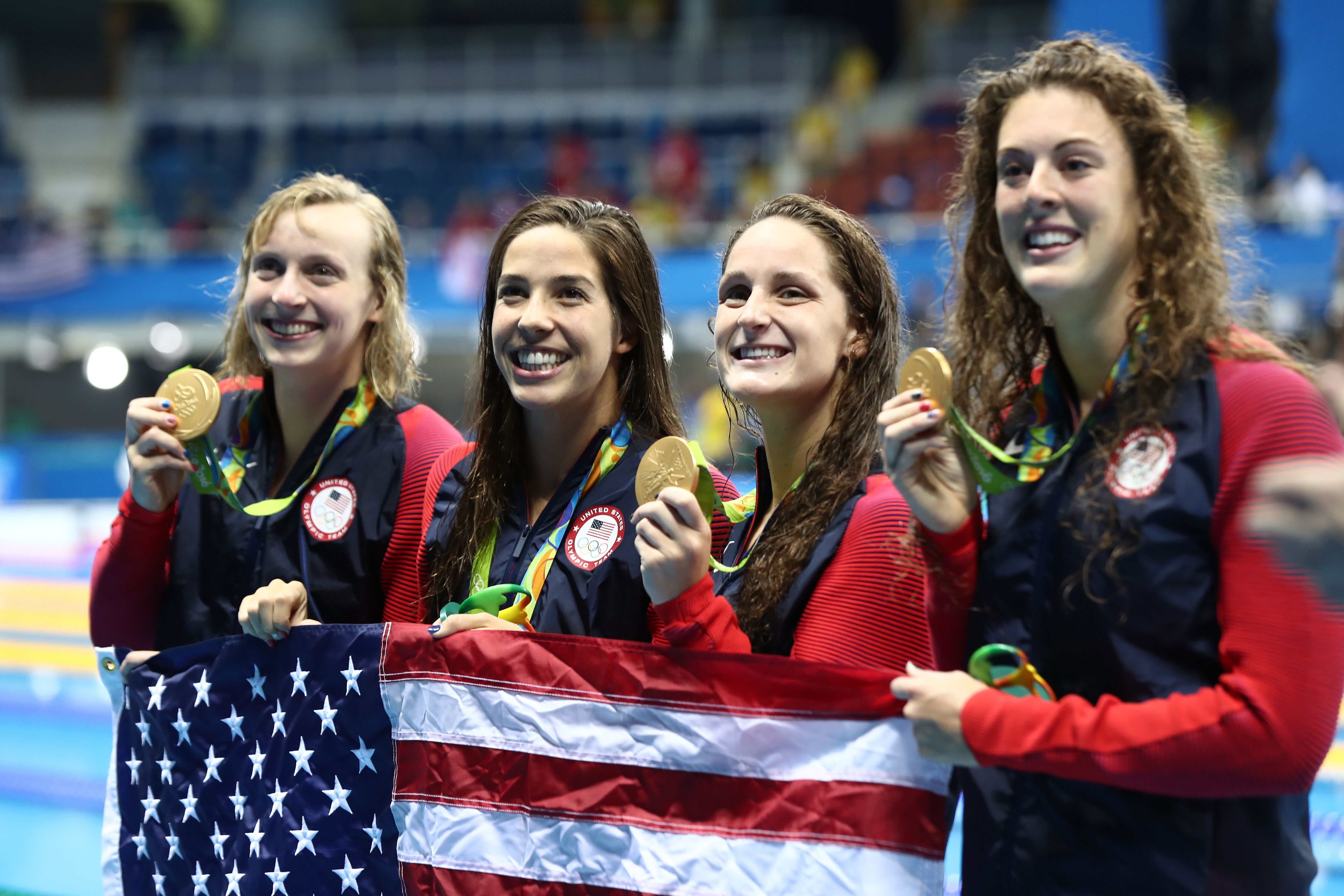 Gold medalists Allison Schmitt, Leah Smith, Maya Dirado, and Katie Ledecky of the United States pose on the podium.
