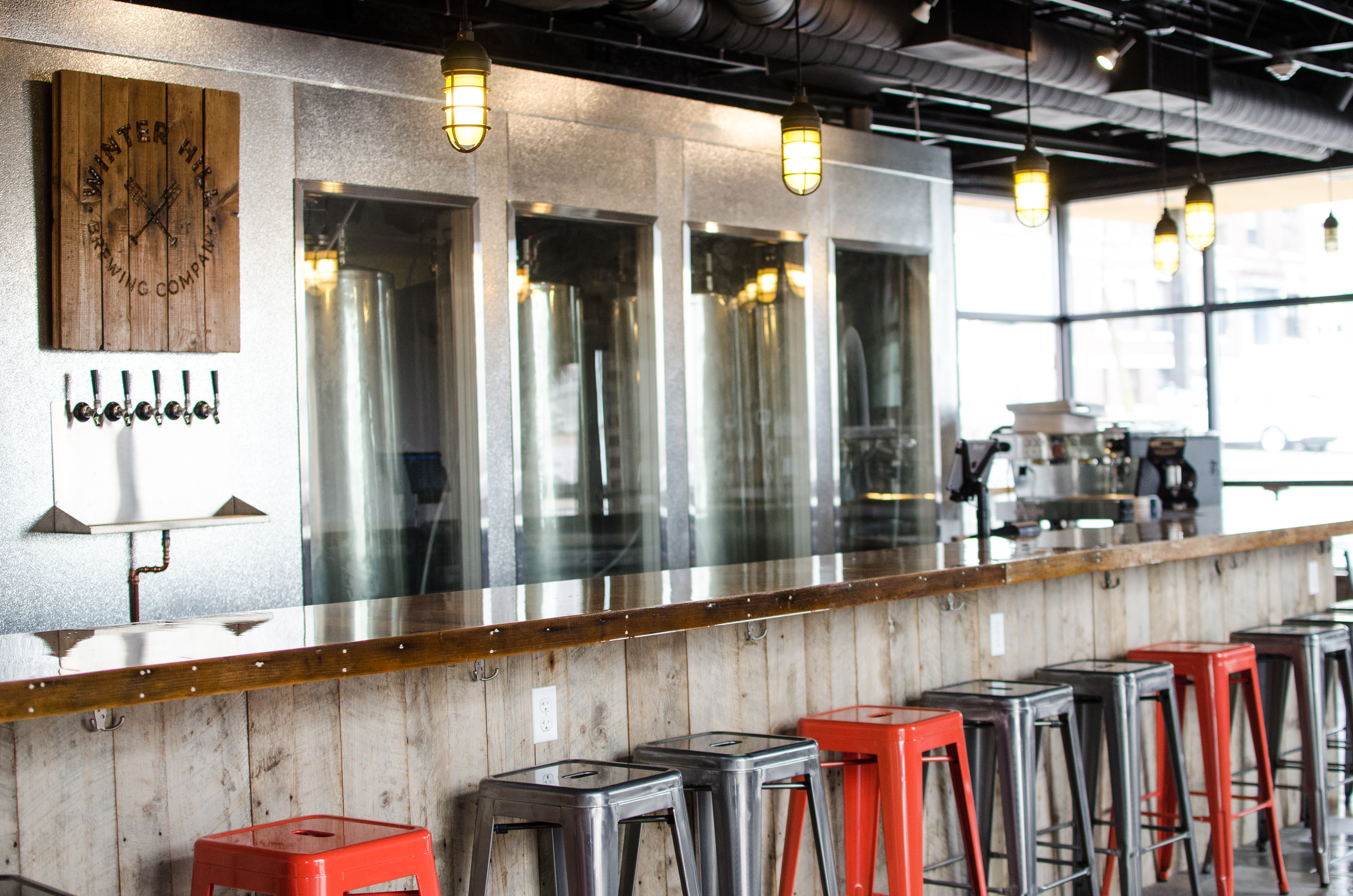 Gray and red backless metal stools line up against a wooden bar with a view of tap handles and brewing tanks