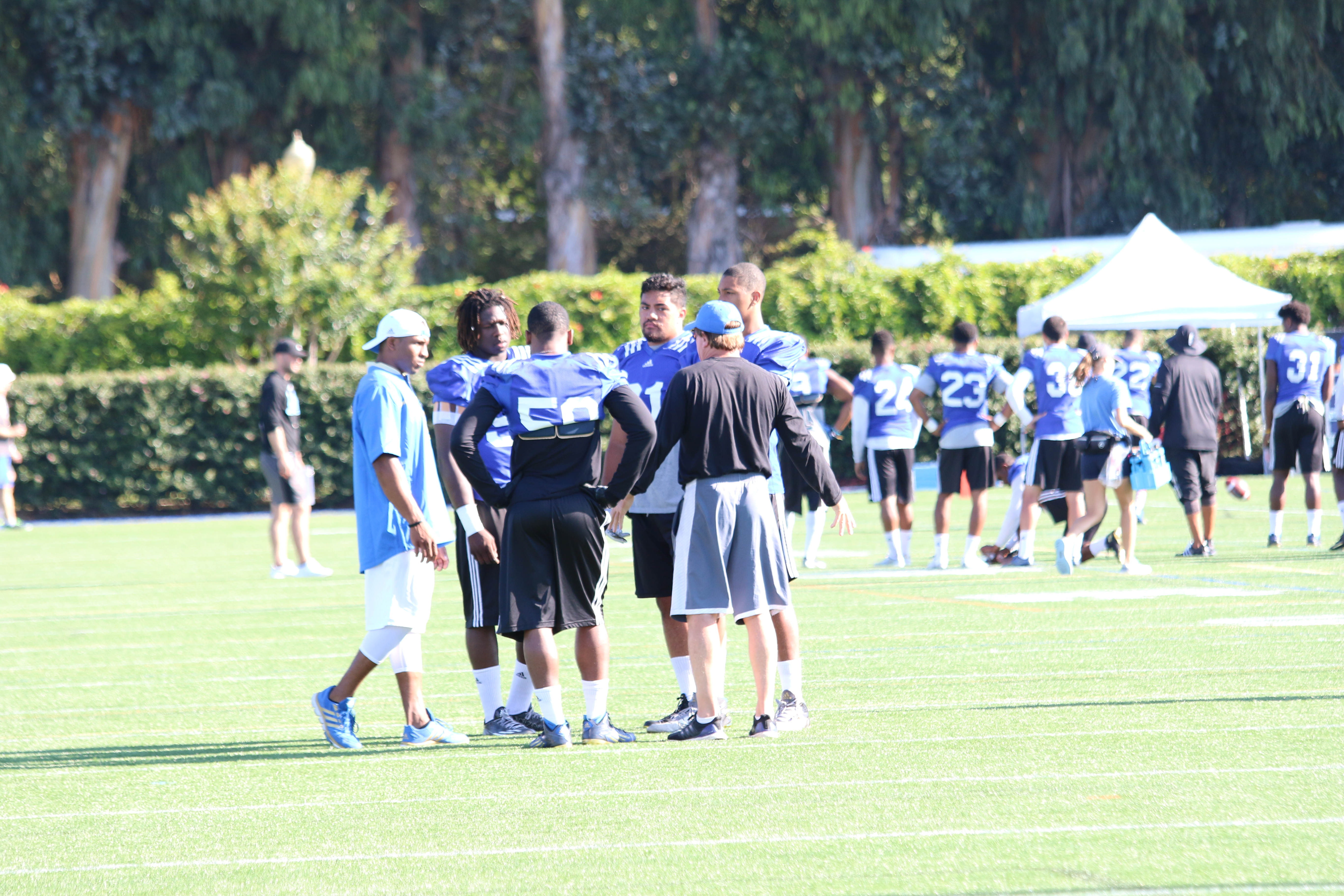 Tom Bradley coaching Tak McKinley and several other defensive players.