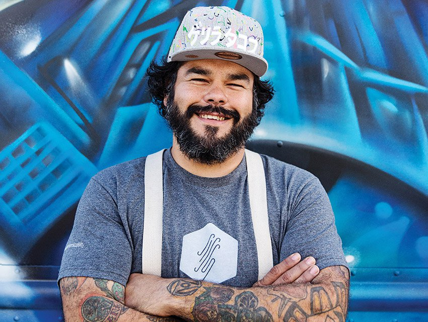 Chef Wes Avila stands against a blue graffiti wall, wearing a hat.