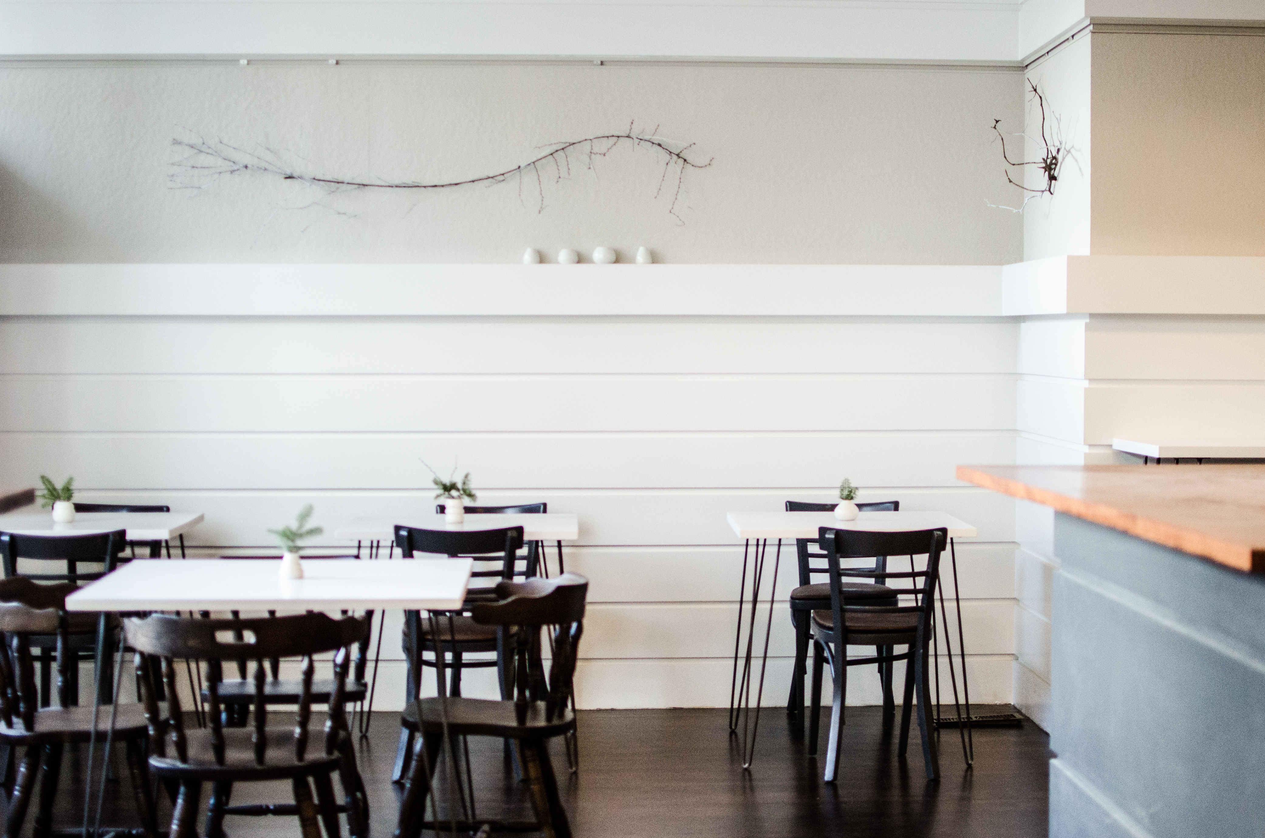 Interior of a well-lit restaurant with minimalist decor and white and off-white walls