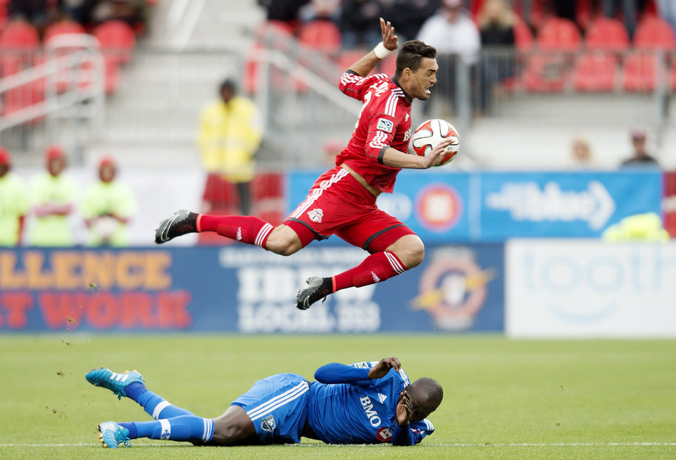 Toronto FC's Gilberto, top, leaps over Montreal Impact's Hassoun Camara after being tackled. (AP Photo/The Canadian Press, Darren Calabrese)