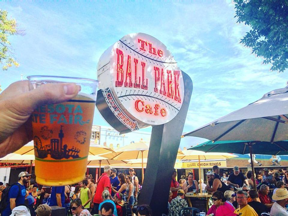 A hand holds up a beer next to the baseball shaped neon sign for the Ball Park Cafe on a busy fair day