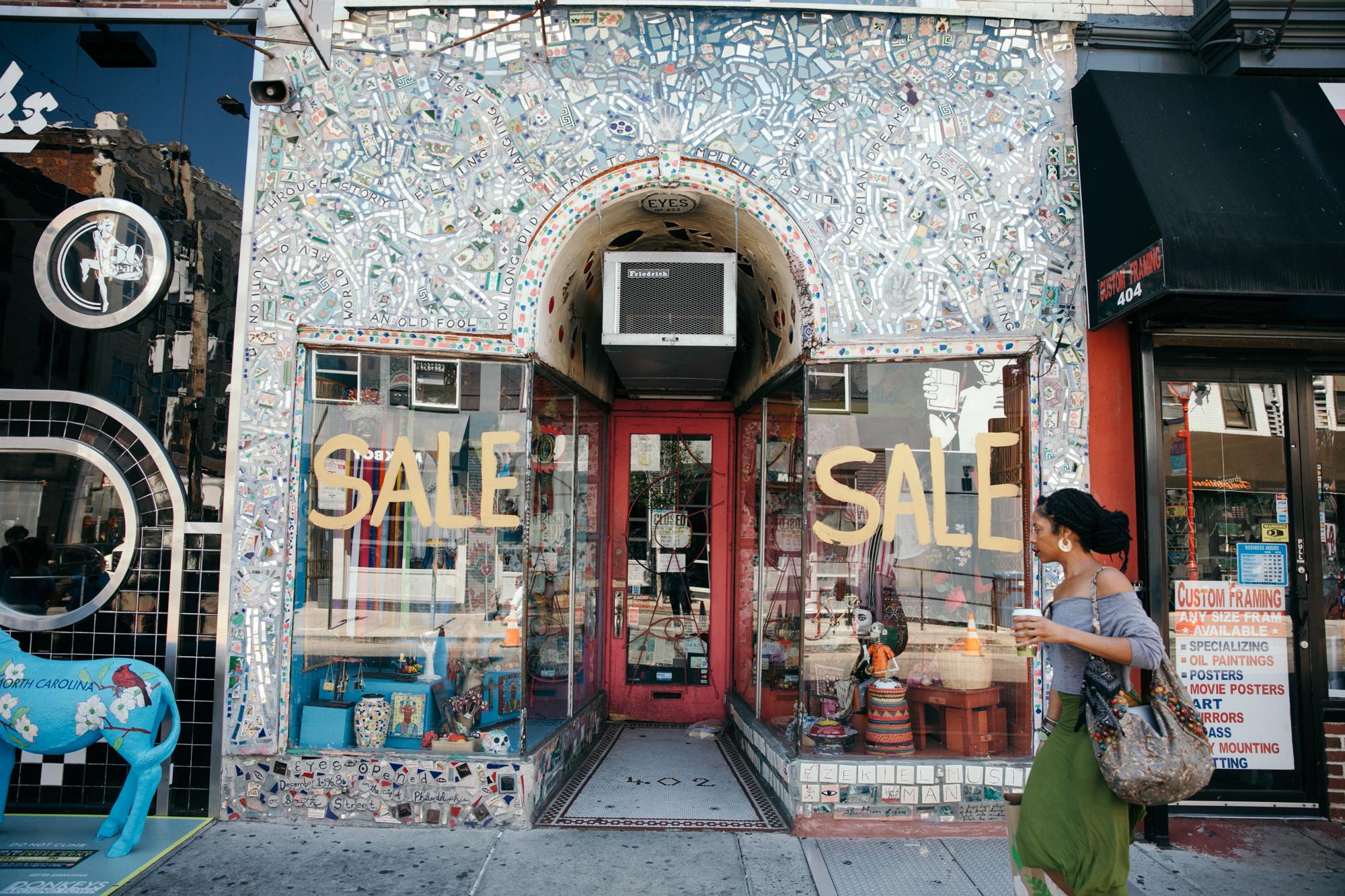A woman walks by Eyes Gallery shop on South Street.