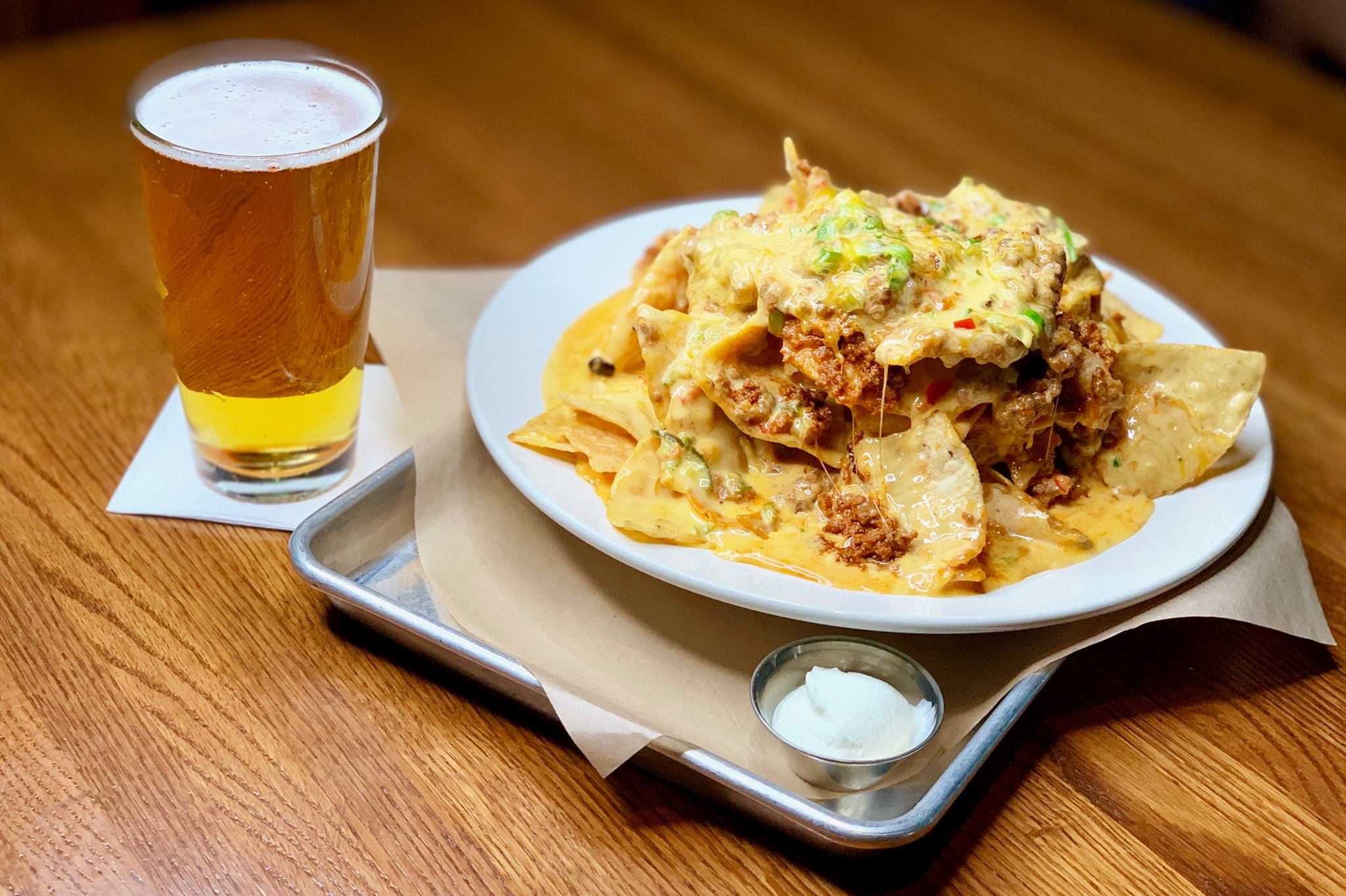 A glass of beer and a plate of nachos