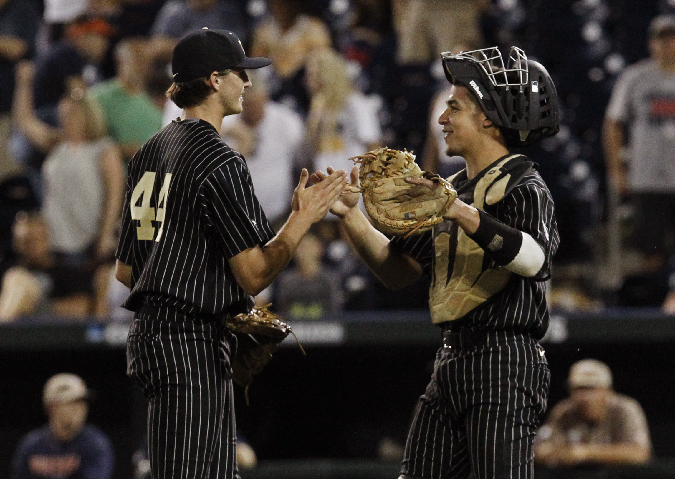 Karl Ellison (right) giving high fives to his pitcher, Kyle Wright (left).