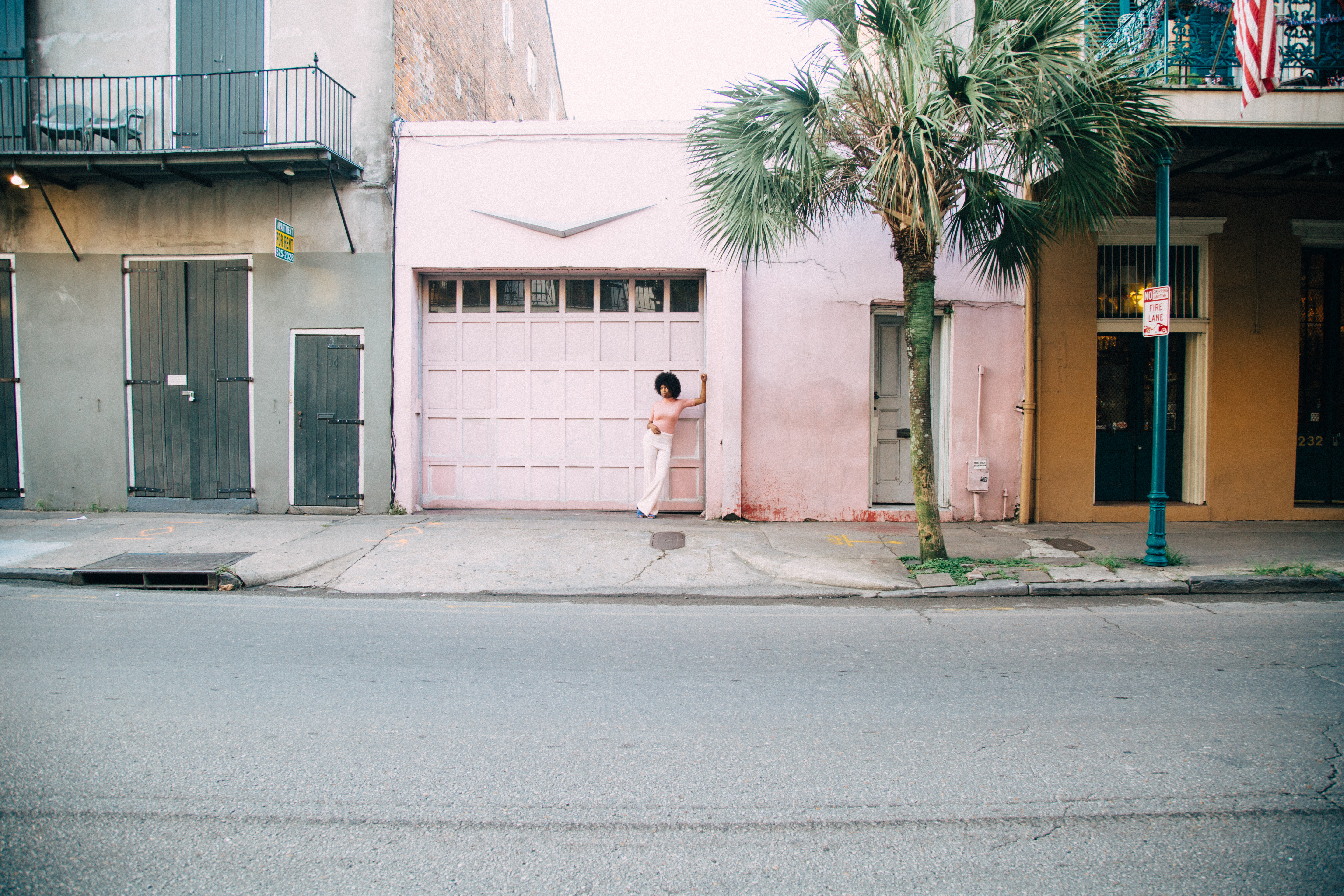 A woman wearing pink stands in front of a pink painted building in New Orleans.
