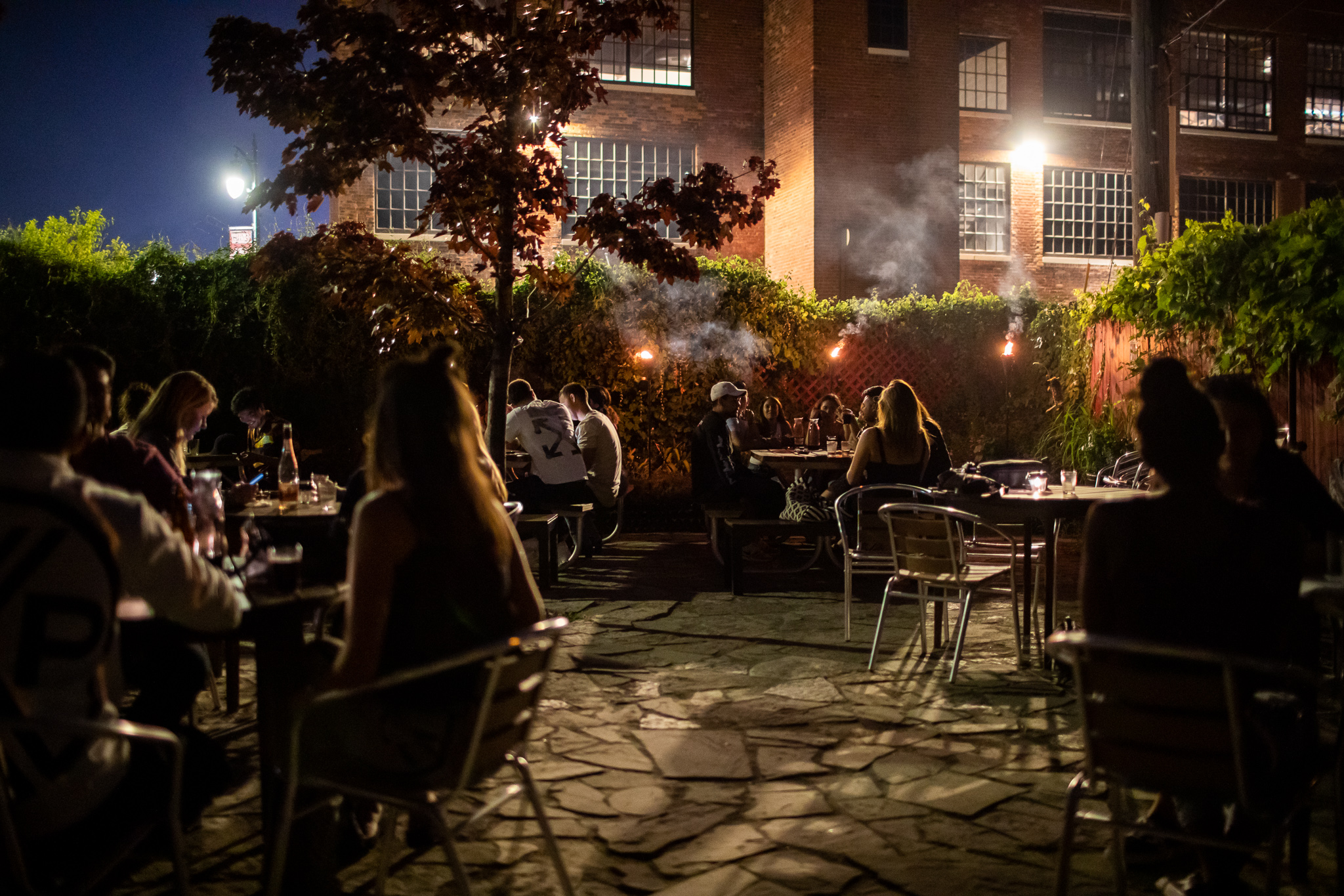 it's twilight on the motor city wine patio and three tiki torches near the ivy covered fence cast a light over the picnic tables and round patio tables filled with customers drinking wine and talking.