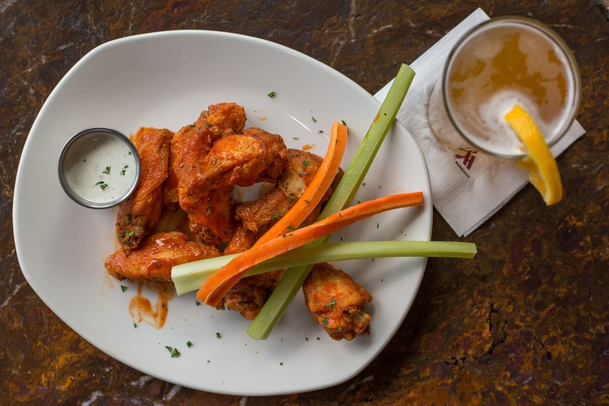 chicken wings in buffalo sauce, celery, carrots, and a beer on the side garnished with citrus wedge