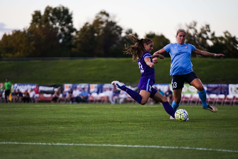 Kristin Grubka attempts to block a shot from Alex Morgan