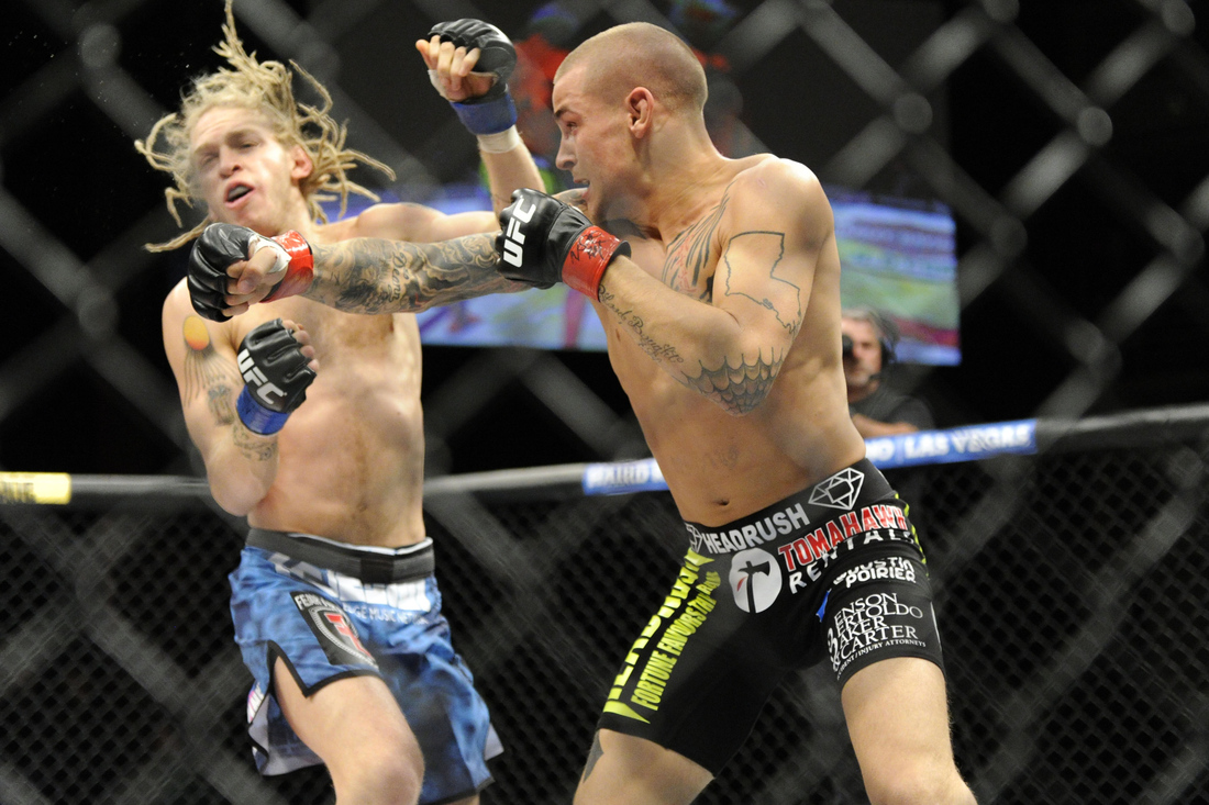Dustin Poirier (right) punches Jonathan Brookins (left) at the TUF 16 Finale last night