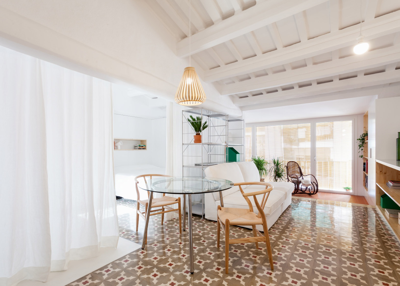 High-ceilinged with exposed beams and white walls, the flat features an open plan with traditional tiling and curtained zones.