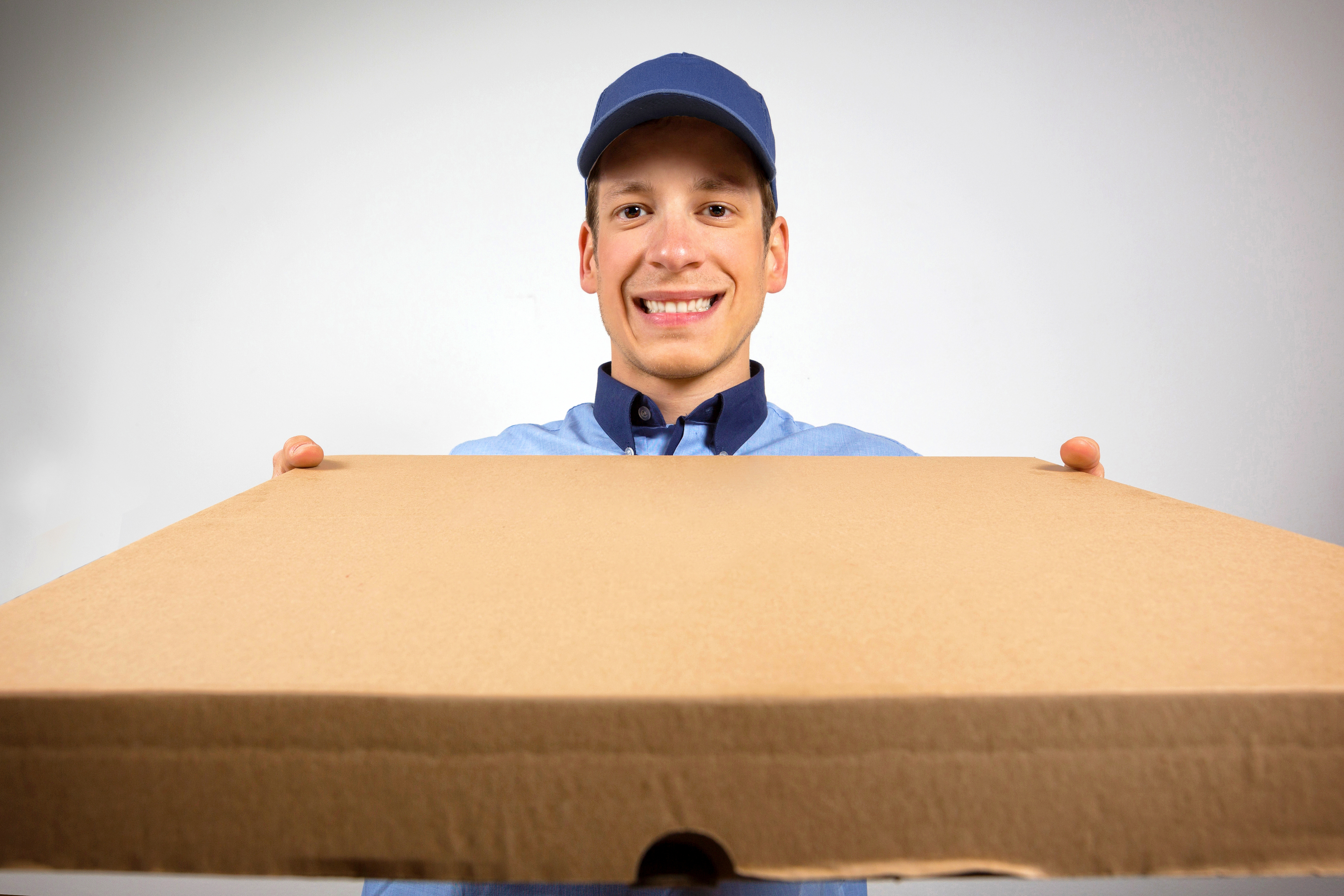 Delivery boy holding out a cardboard pizza box