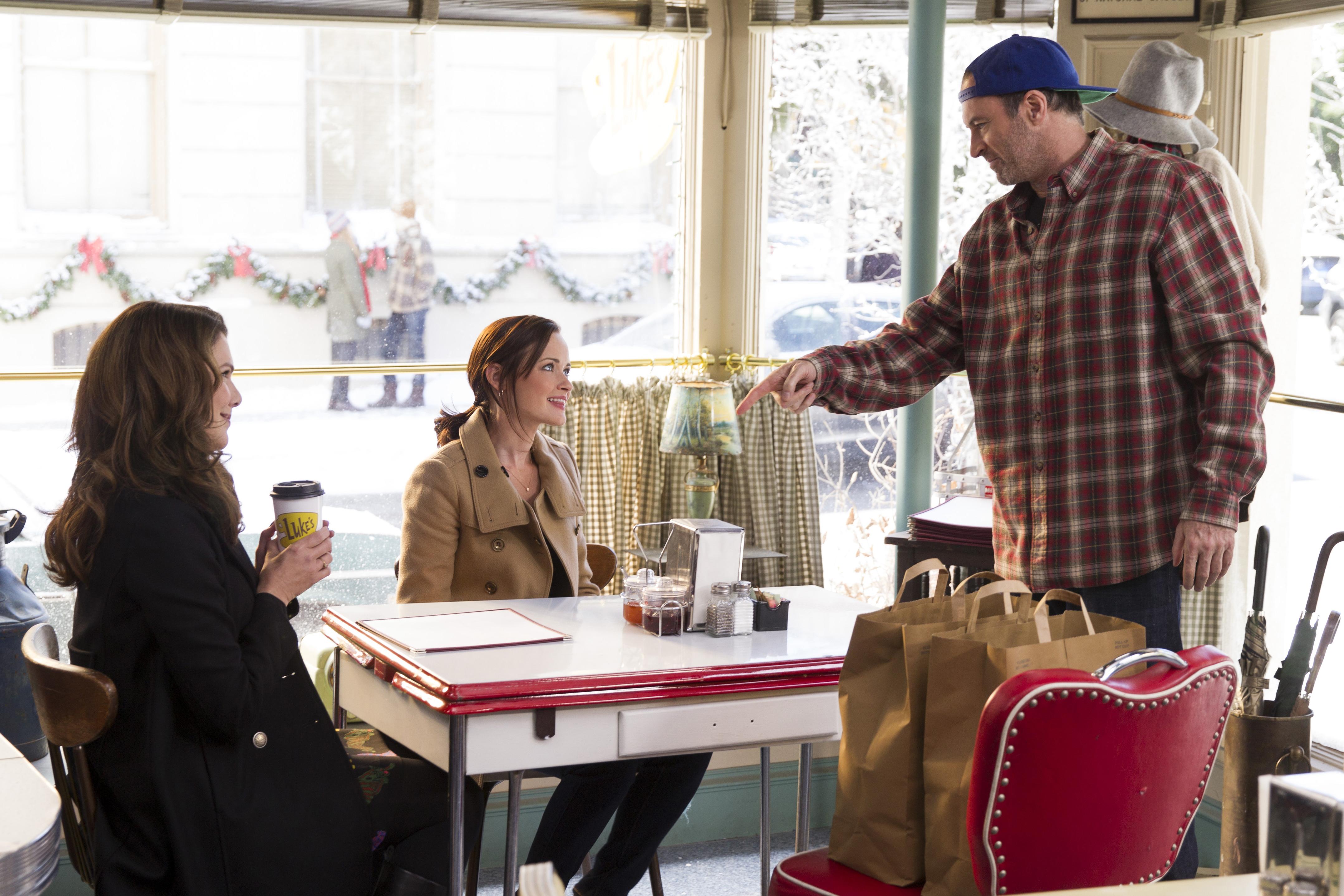 A Gilmore Girls scene at Luke's Diner, featuring Luke, Lorelai, and Rory.
