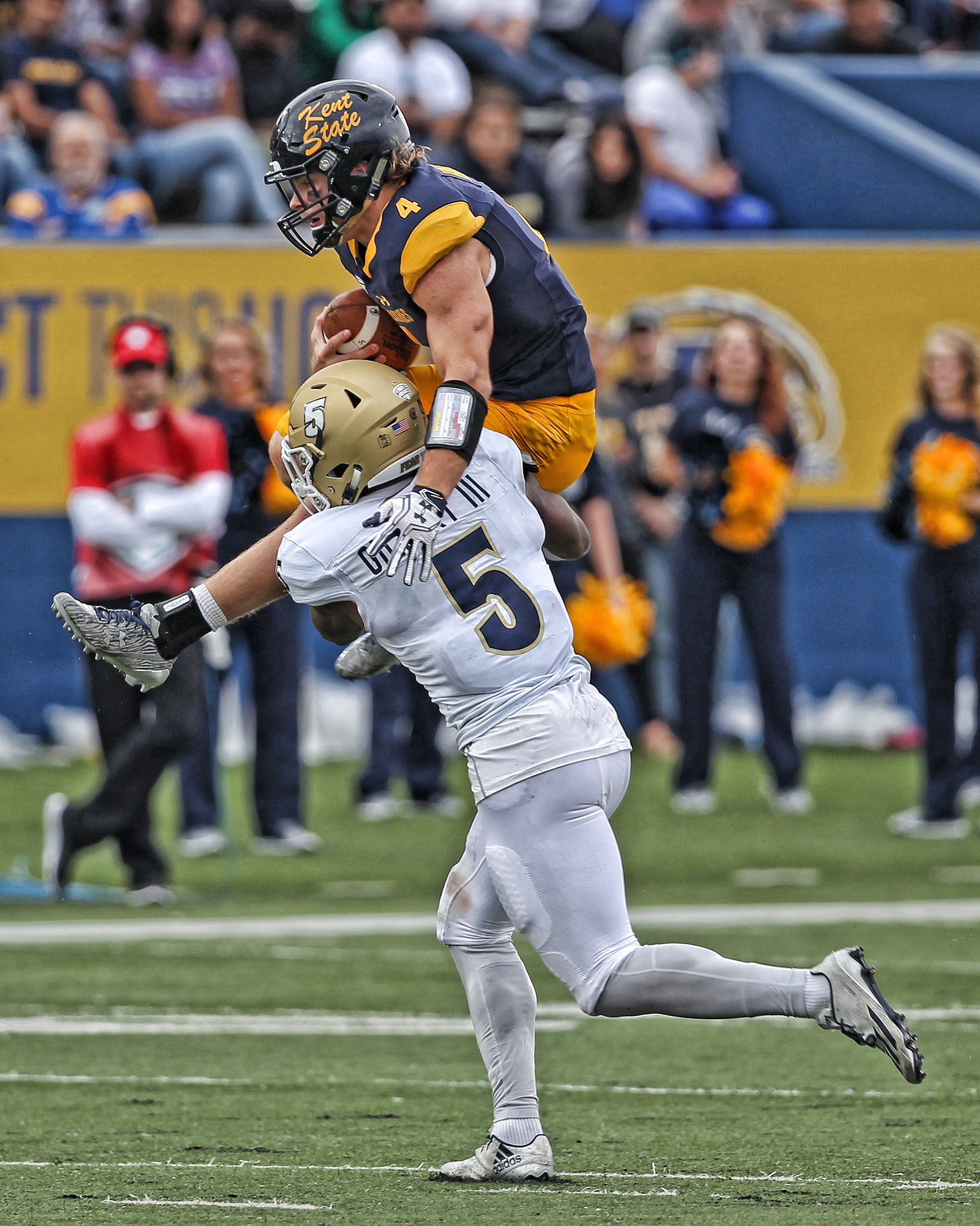 Kent stand in QB Nick Holley attempts to get by Akron's Ulysses Gilbert III.