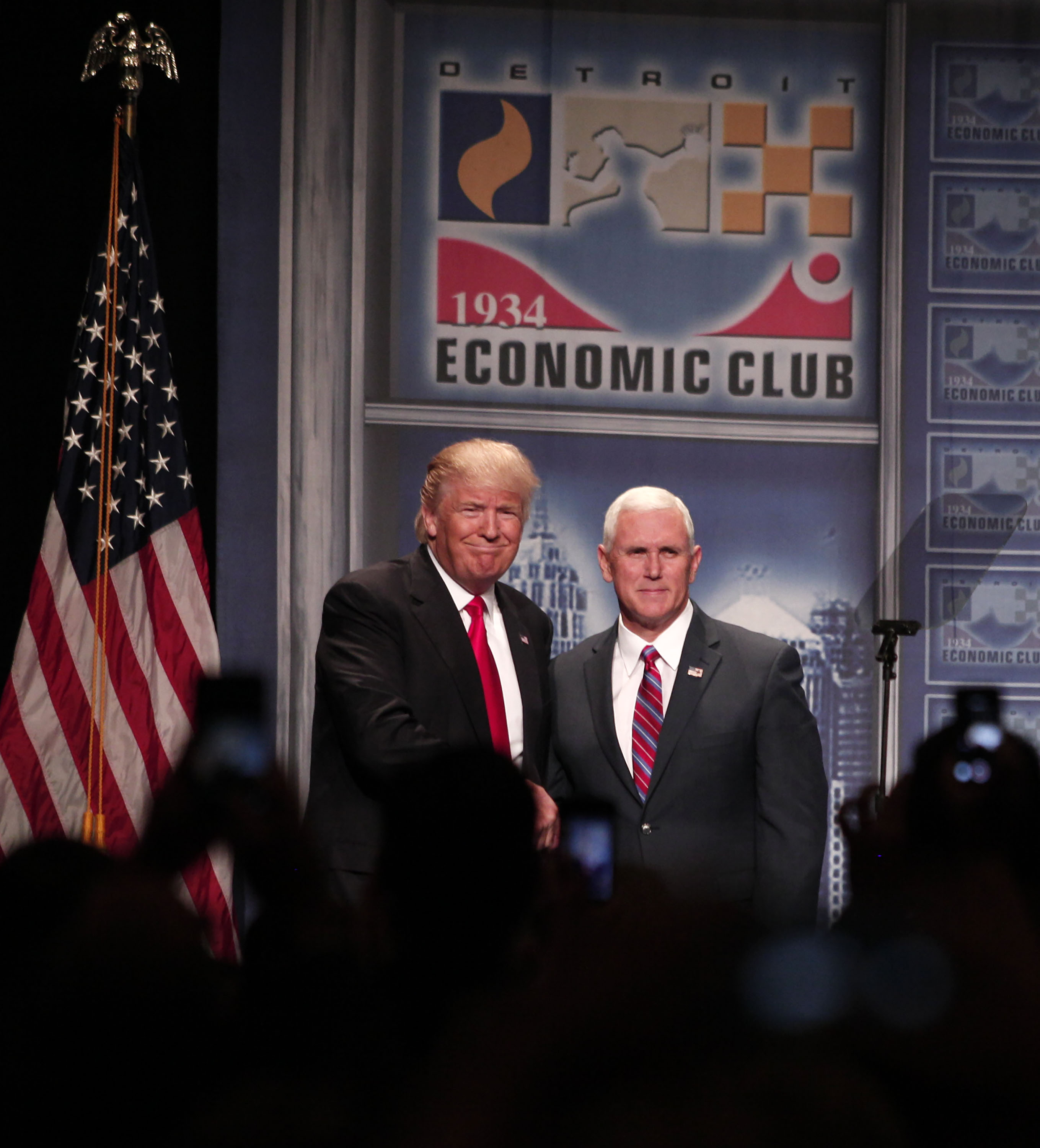 Republican presidential candidate Donald Trump (left) and his vice presidential running mate Indiana Gov. Mike Pence stand on stage together before Trump delivers an economic policy address detailing his economic plan at the Detroit Economic Club August 8