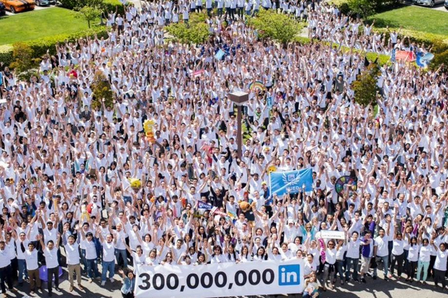 A crowd of people shot from above, mostly caucasian, outside, holding a banner that says 300,000,000 In.
