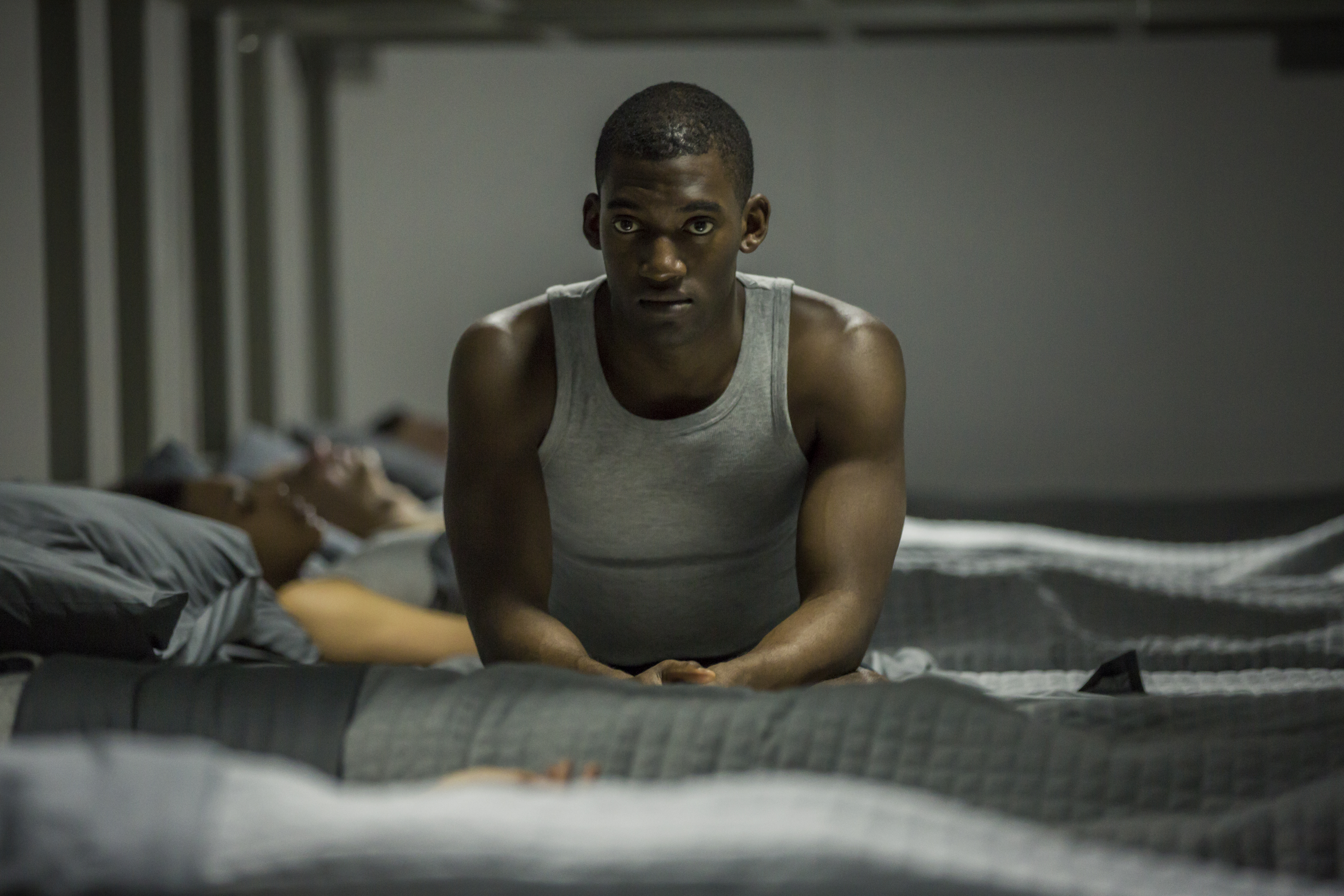 """Malachi Kirby sits on a bed in the Black Mirror episode """"Men Against Fire."""""""