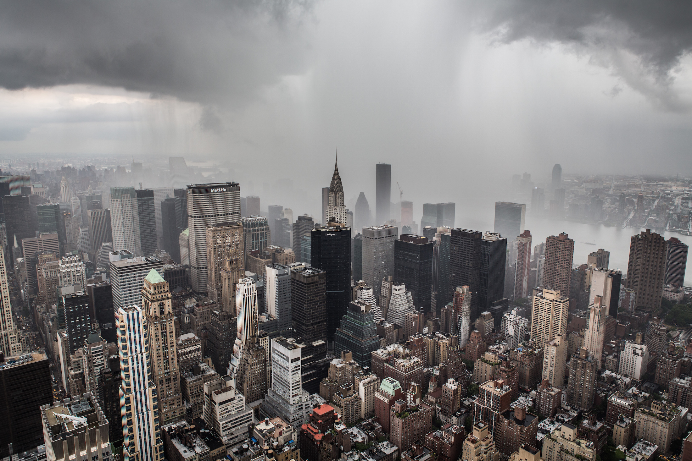 An aerial view of the buildings of New York City in midtown Manhattan. There are buildings of varying heights including the Chrysler Building. There are storm clouds and fog.