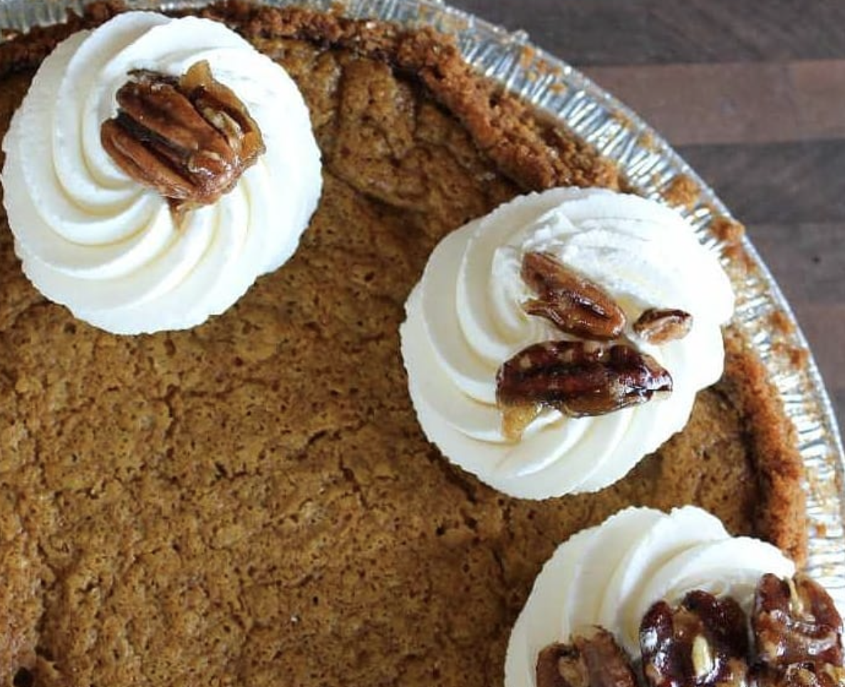 A pumpkin pie with whipped cream dollops and pecans from A La Mode