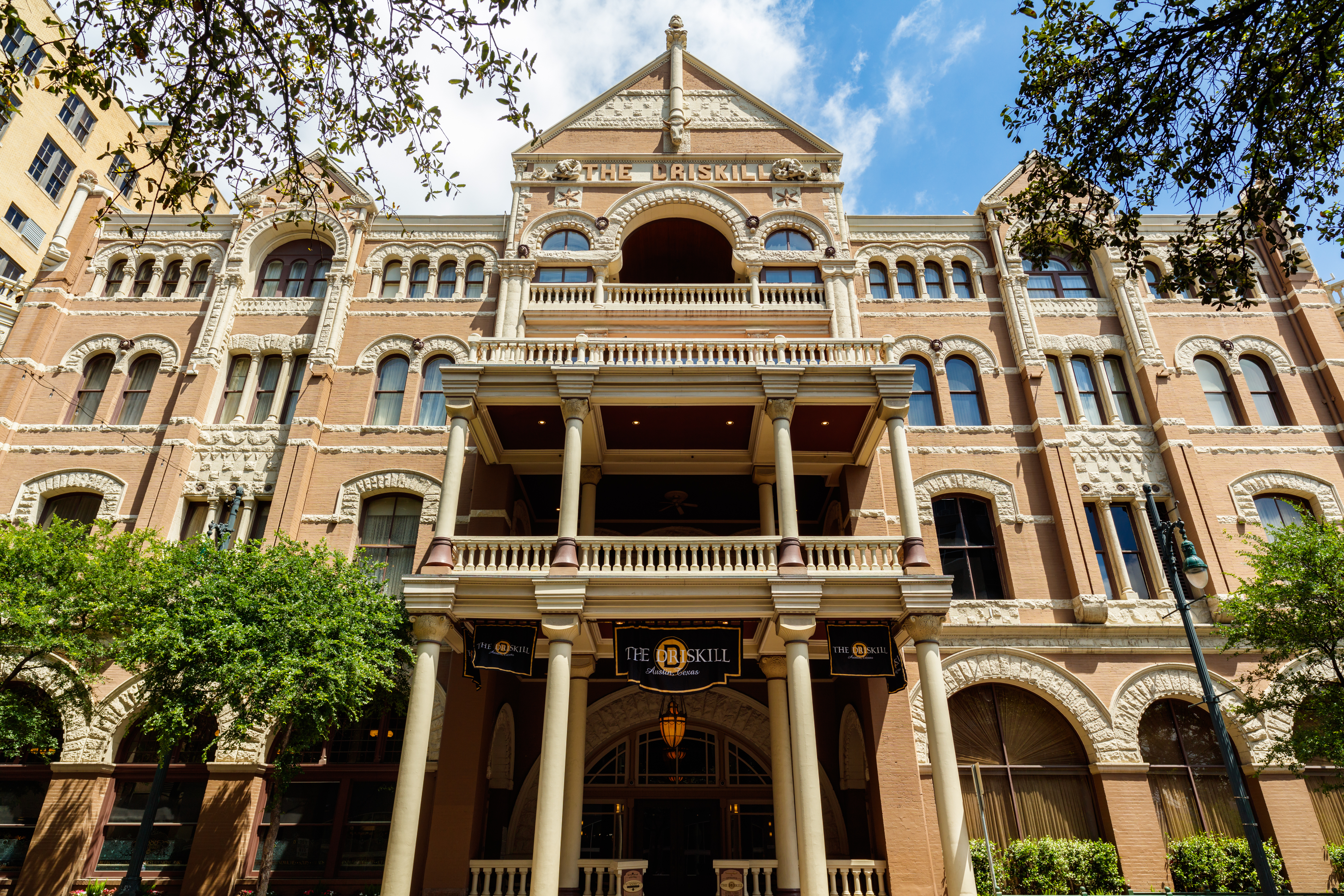 The exterior of the Driskill hotel in Austin. The facade is red brick with multiple windows. There are columns flanking the entrance area.